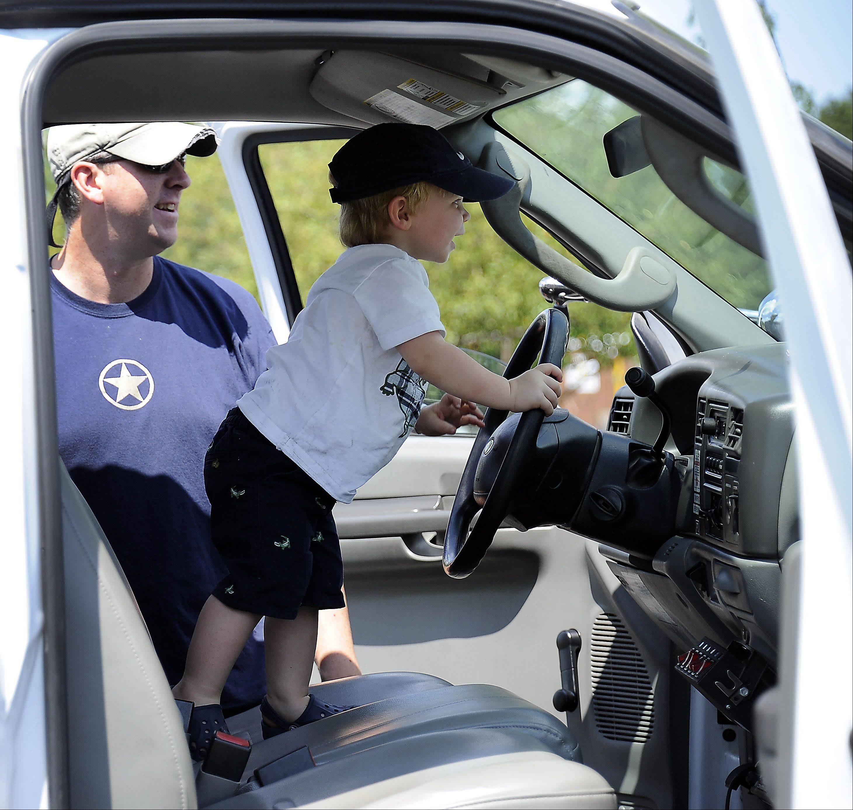 Harrison Rumney grips the wheel of the aerial bucket truck as his dad, Marshall, watches to make sure he doesn't lose control at a previous year's Big Trucks event in Barrington.