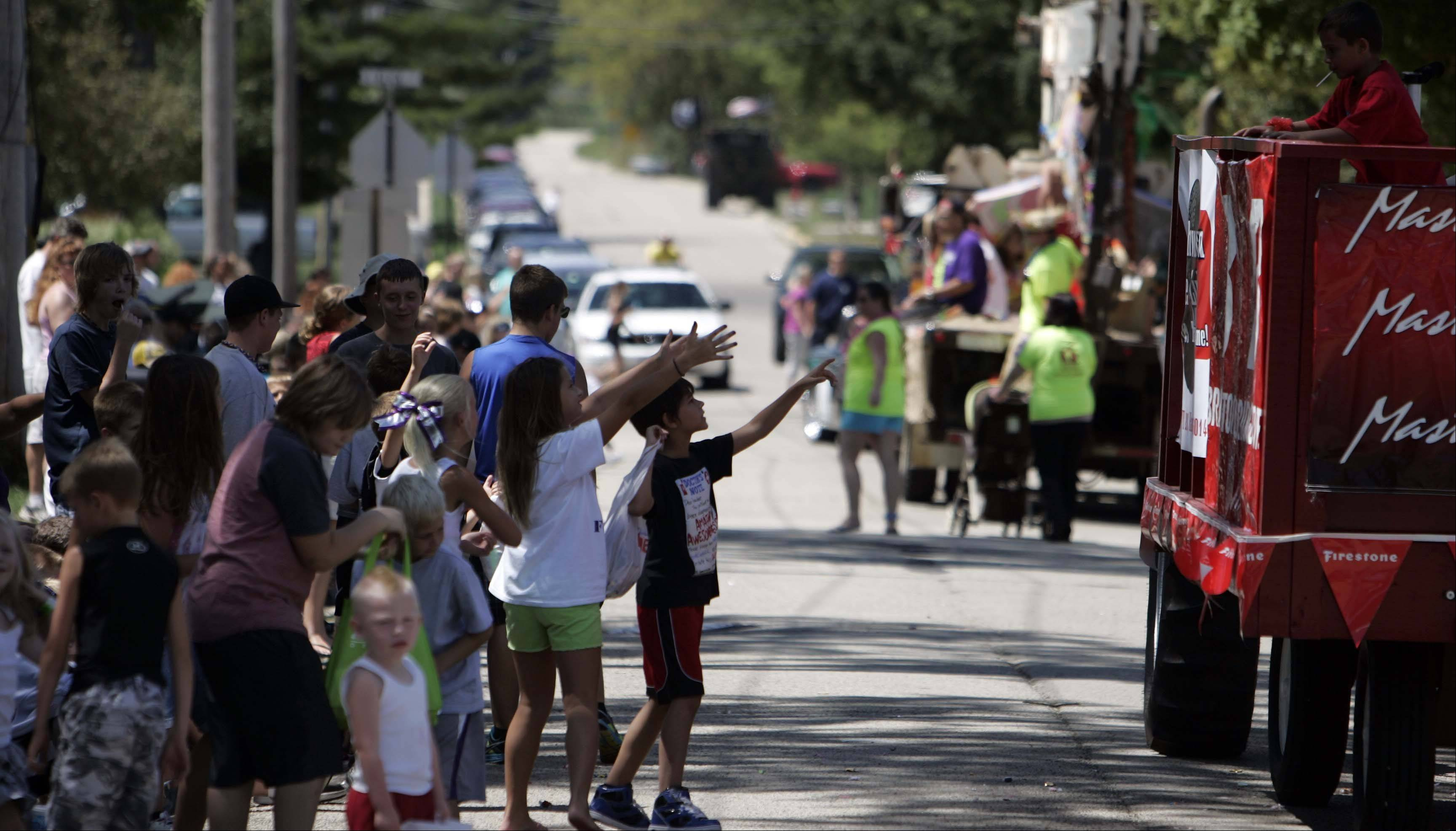 Children reach to grab candy as last year's parade winds toward Bruce Ream Park at Coon Creek Country Days in Hampshire.