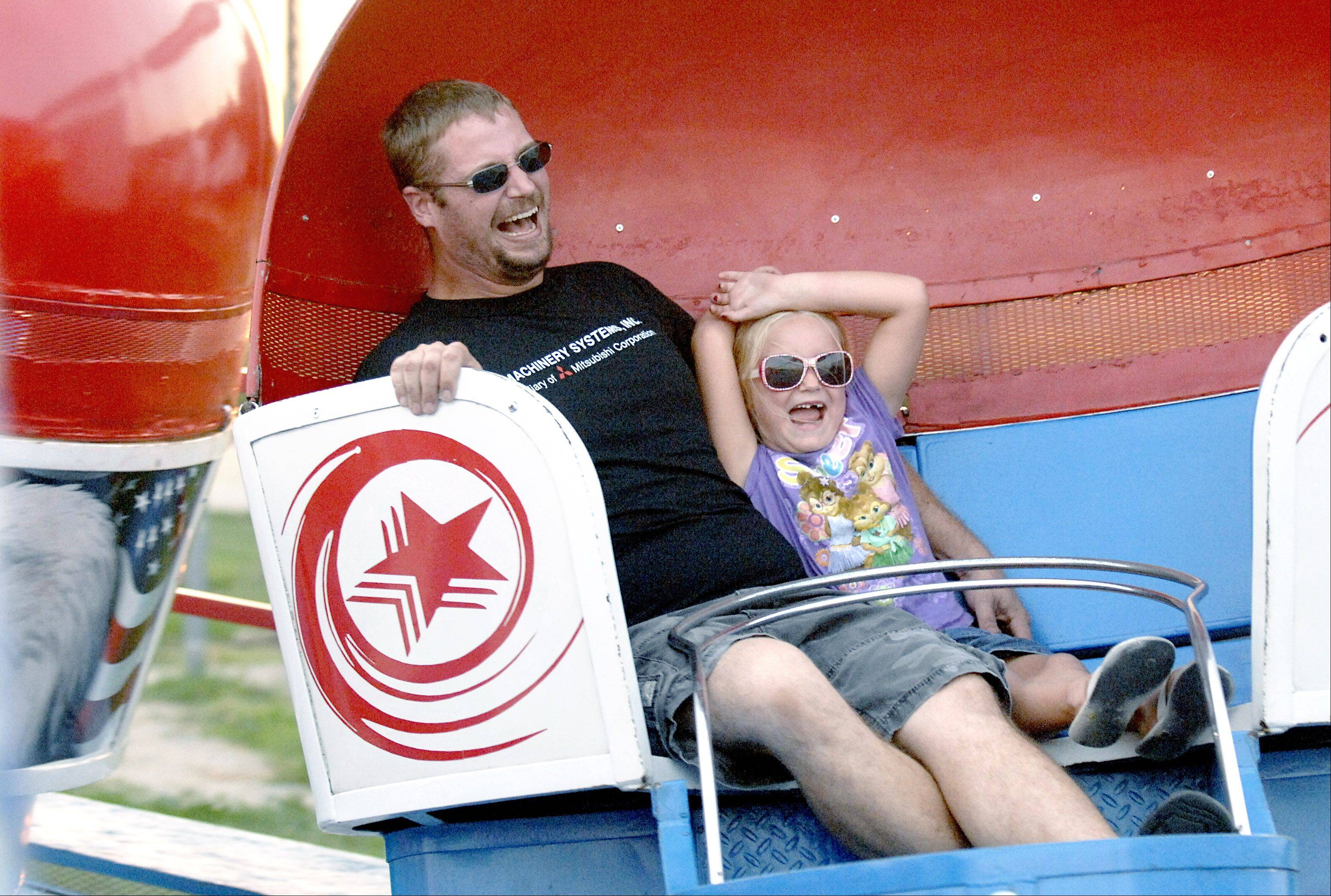 Fred Marwig and his daughter, Ashlyn, 6, of Hampshire, can't keep from laughing as their Tilt-a-Whirl car spins at a high rate of speed during last year's Coon Creek Country Days in Hampshire.