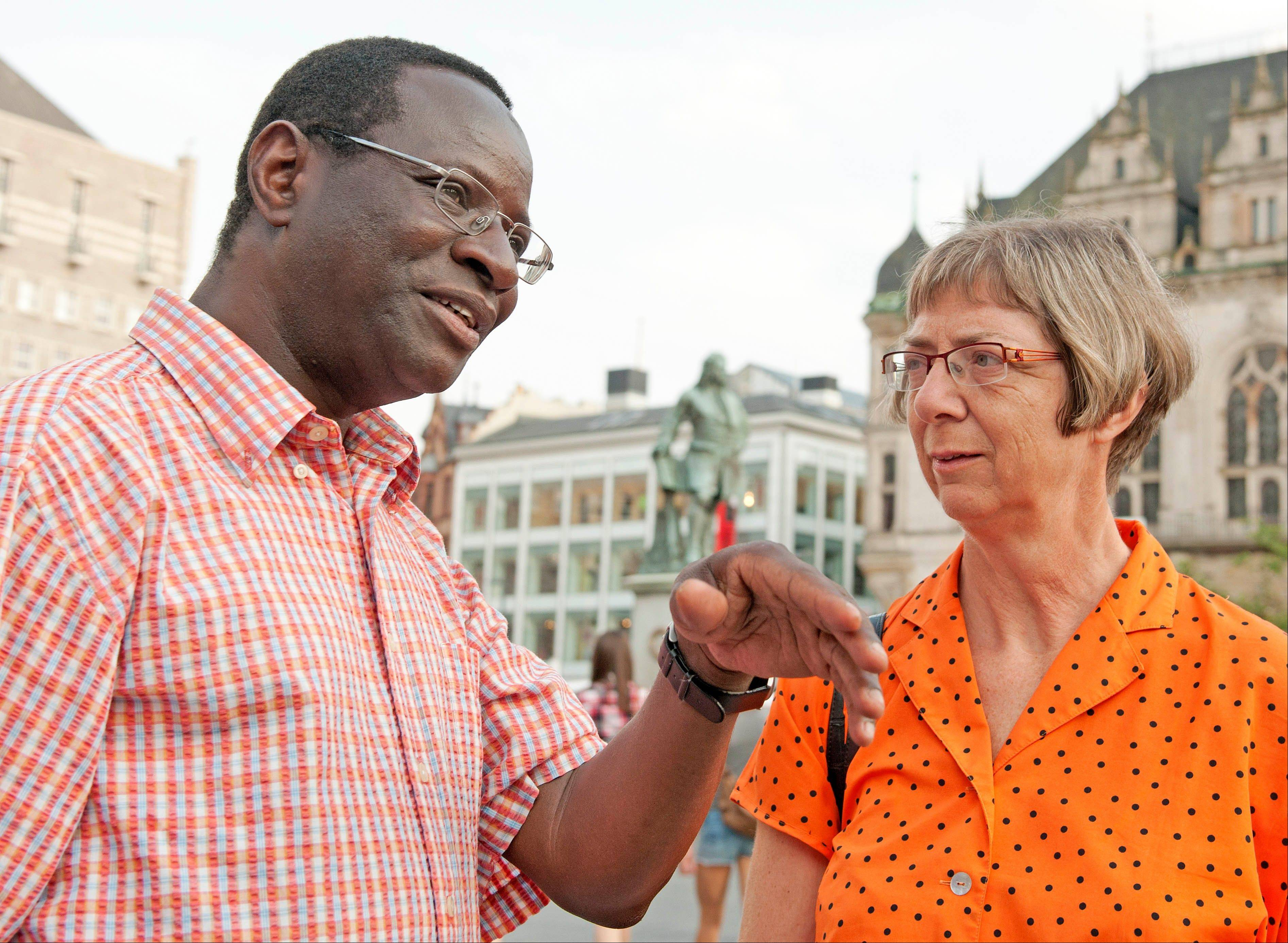 In this picture taken July 25, 2013, Karamba Diaby, a German Social Democratic Party candidate talks with citizen Heidi Juergens during an election campaign in Halle, central Germany, Thursday, July 25, 2013. He was born in Senegal and moved to the former GDR to study at the University of Leipzig. Diaby, now 51, is campaigning for a Bundestag seat to become the country's first black member of Parliament.