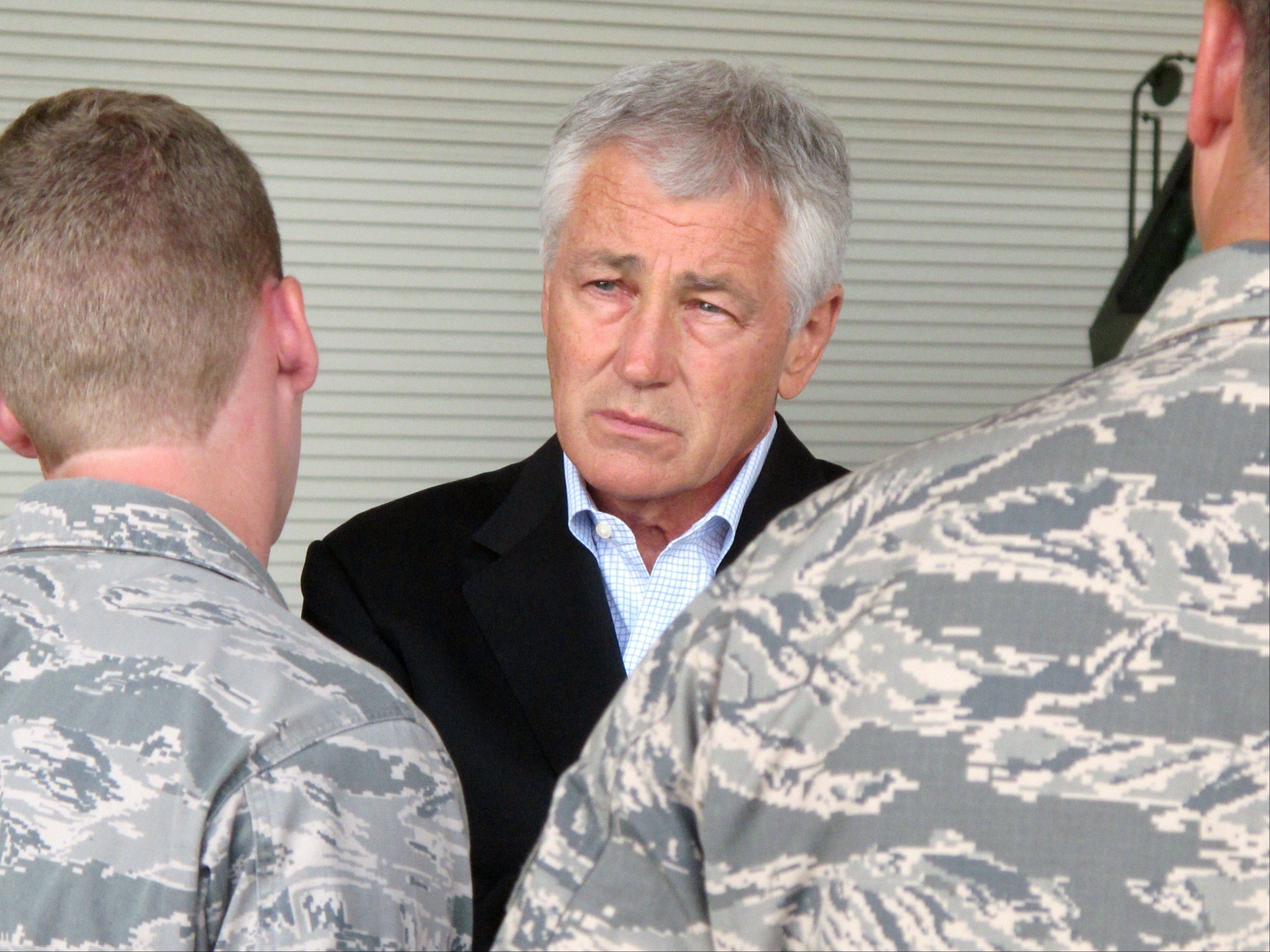 In this July 17, 2013, file photo. Defense Secretary Chuck Hagel talks with Air Force personnel at Joint Base Charleston near Charleston, S.C. A second, deeper round of automatic budget cuts is on its way, and it's going to hit the Pentagon hard.