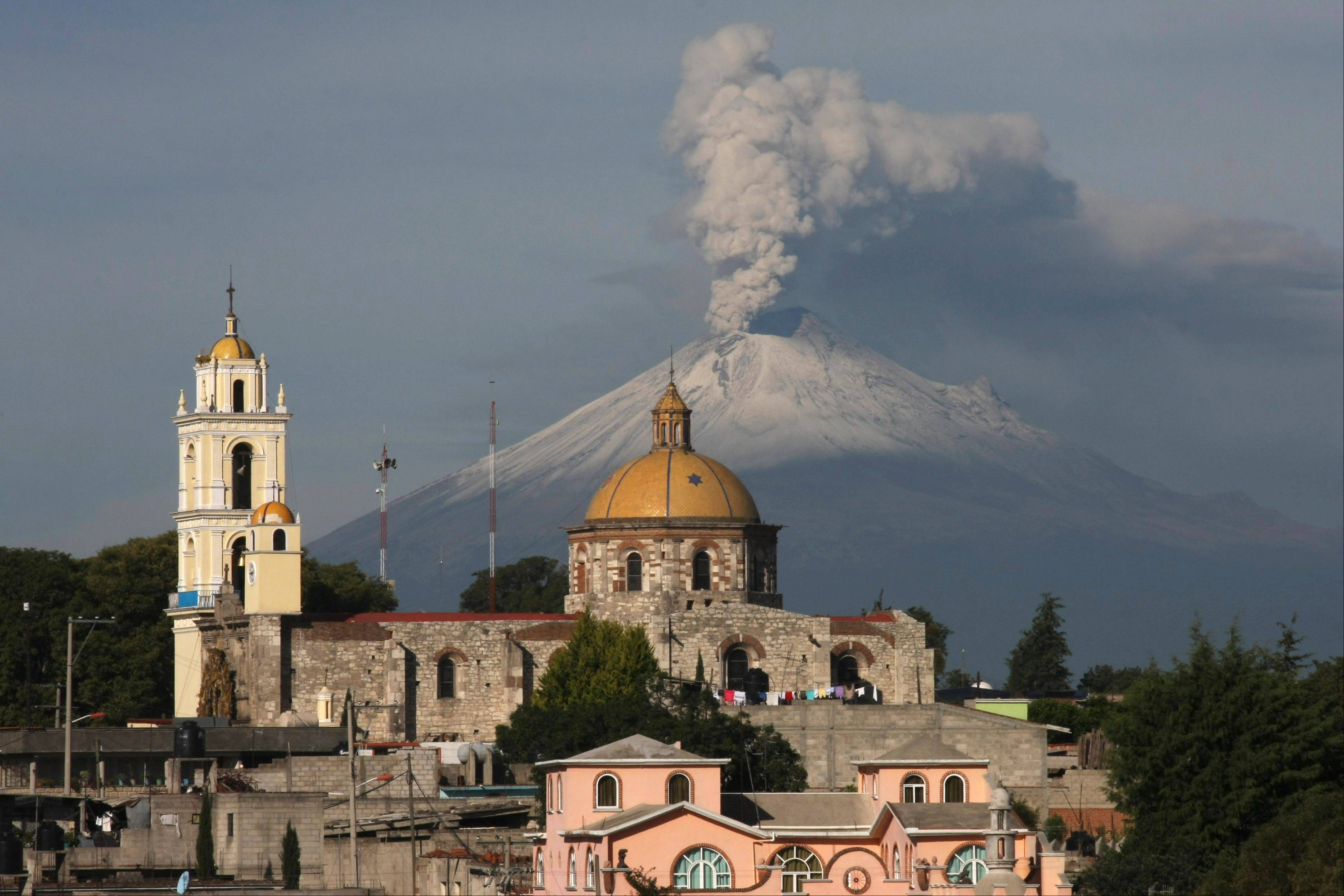 In this July 9, 2013 file photo, the church in the town of San Damian Texoloc, Mexico stands near Popocatepetl volcano spewing ash and vapor. Mexico's disaster prevention center says Popocatepetl has been active for at least 500,000 years. The biggest danger for those nearby are mudslides and swift-moving clouds of gas.