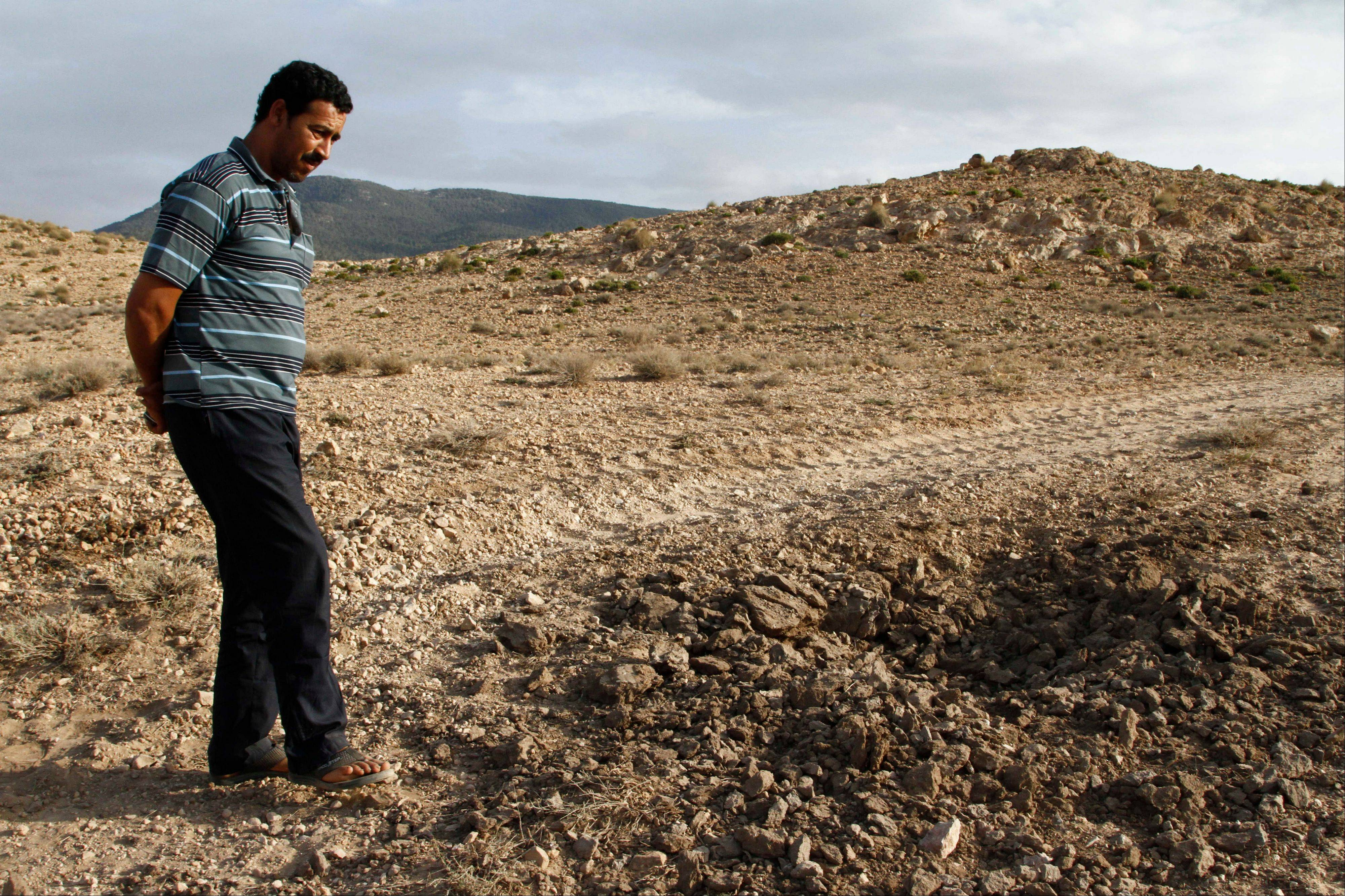 Ezzedine Messaoudi examines on June 24, 2013 the crater left by the roadside bomb that injured his brother and killed several of his sheep earlier that month while the army was searching for jihadis hiding out in Tunisia's Jebel Chaambi region near Algeria. Tunisia, the last, best hope for the Arab Spring, is under increasing threat of an Islamic insurgency.