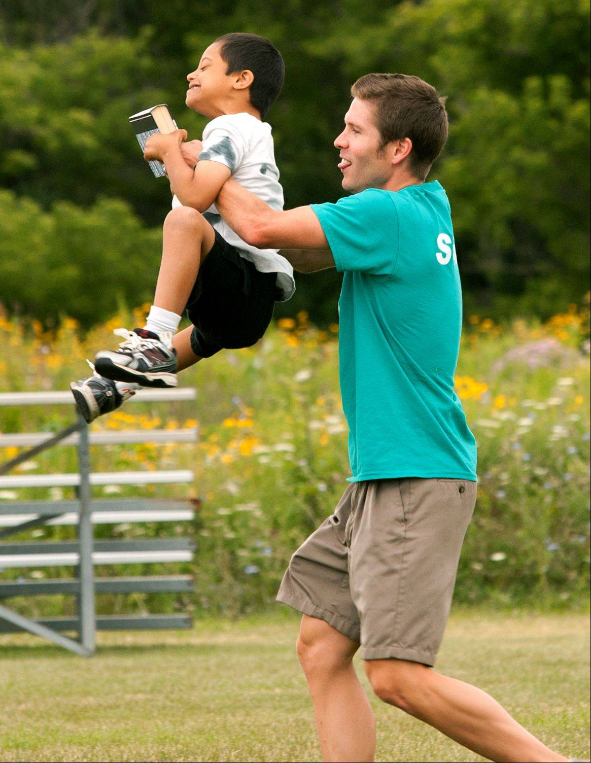 Instructor Daniel Rische carries a member of the Western DuPage Special Recreation Association during the fifth annual WAYS Salute to the Olympics, held at Carol Stream's Red Hawk Park.