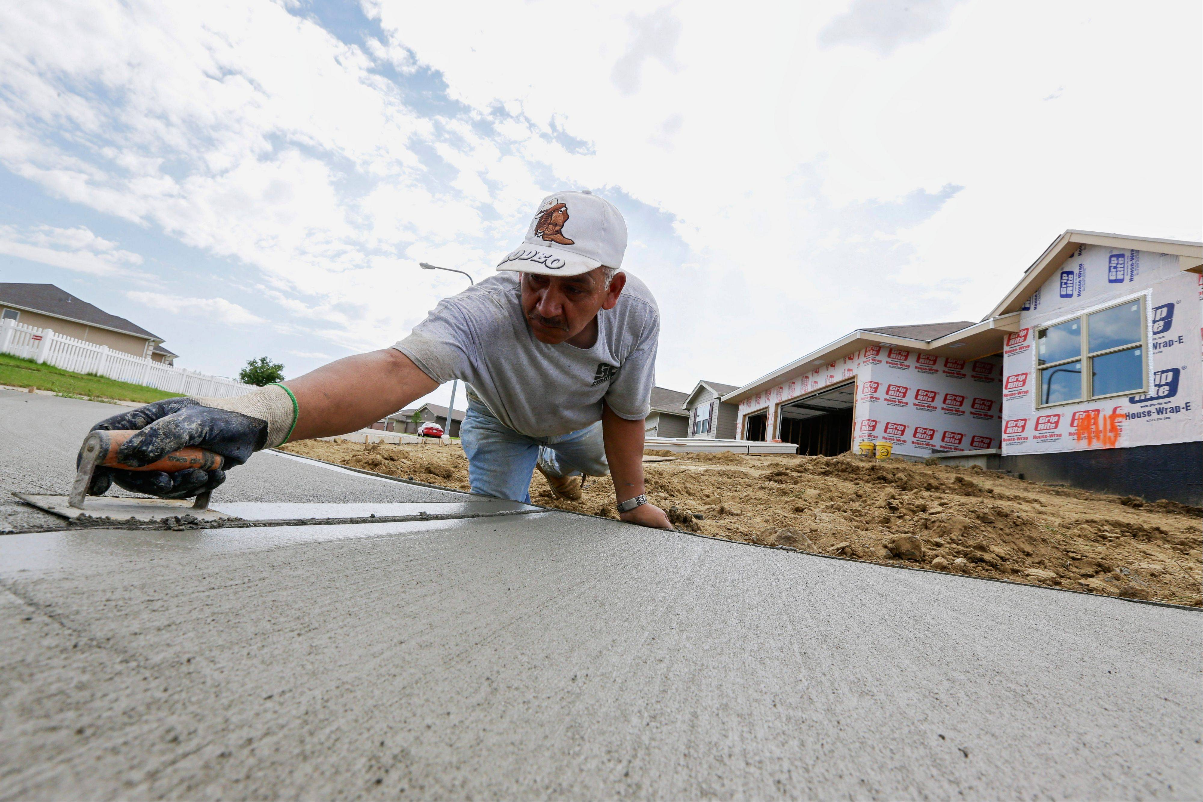 A sidewalk gets shaped Thursday in front of new construction in Omaha, Neb. Conductors of a monthly survey of business leaders in nine Midwest and Plains states say the region's economy will grow in the coming months.