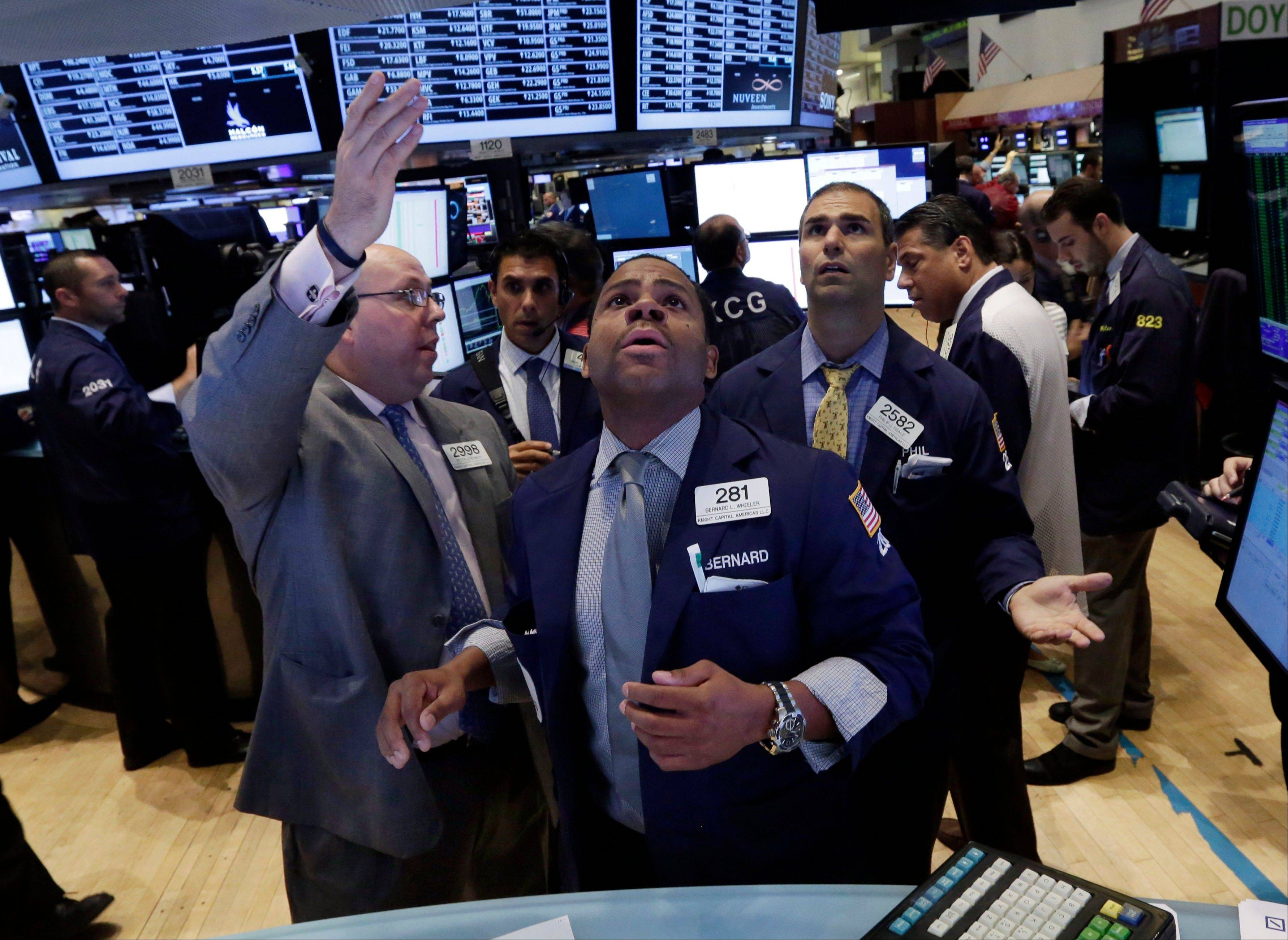 Specialists Peter Kennedy, Bernard Wheeler, and Philip Finale, confer on the floor of the New York Stock Exchange.