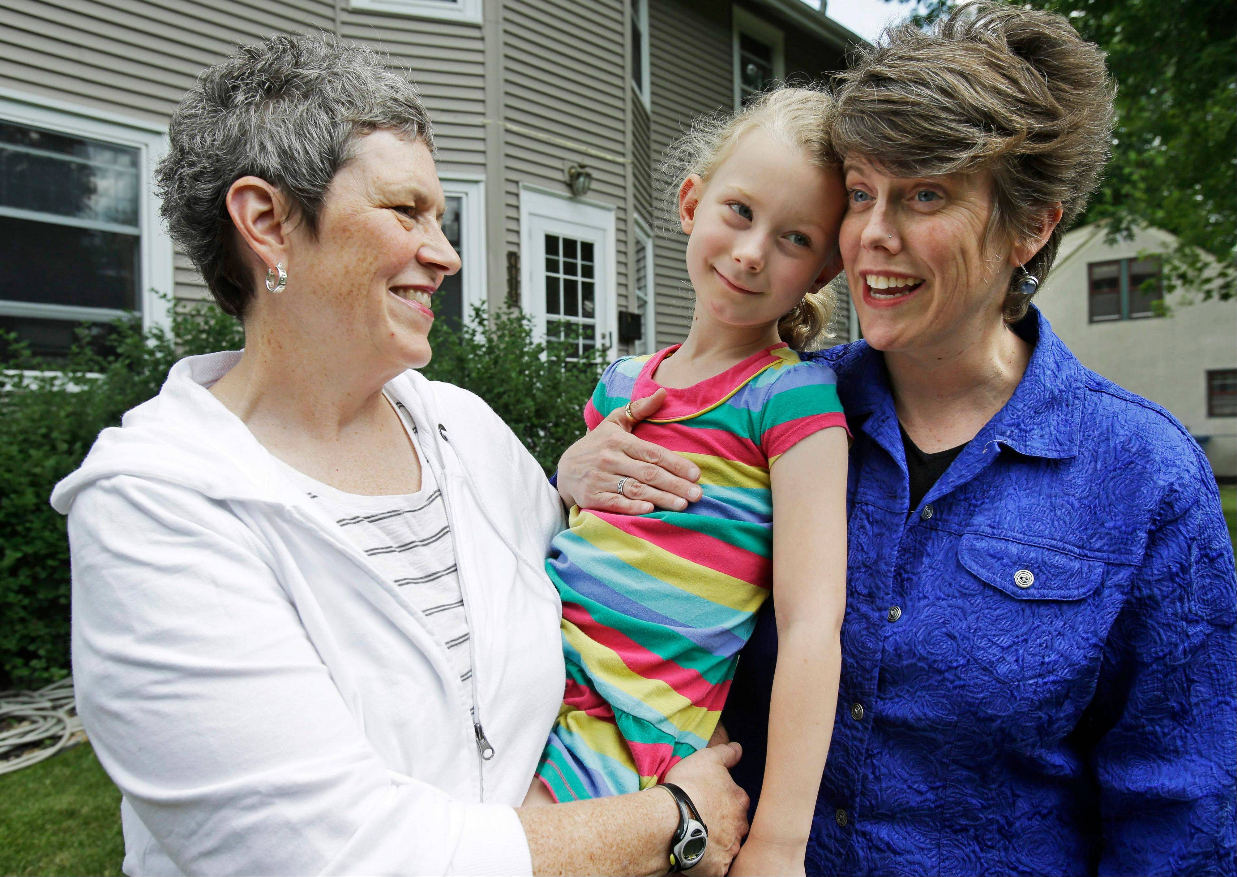 Maggie George, left, and Rebecca Voelkel with their 6-year-old daughter Shannon at their Minneapolis home. Maggie and Rebecca have married each other twice, first ceremonially in their Minneapolis church in 2006, then legally while visiting San Francisco five years ago. Now the couple is mulling whether to do it all again — or to simply sleep through it — when gay marriage becomes legal in Minnesota this week.
