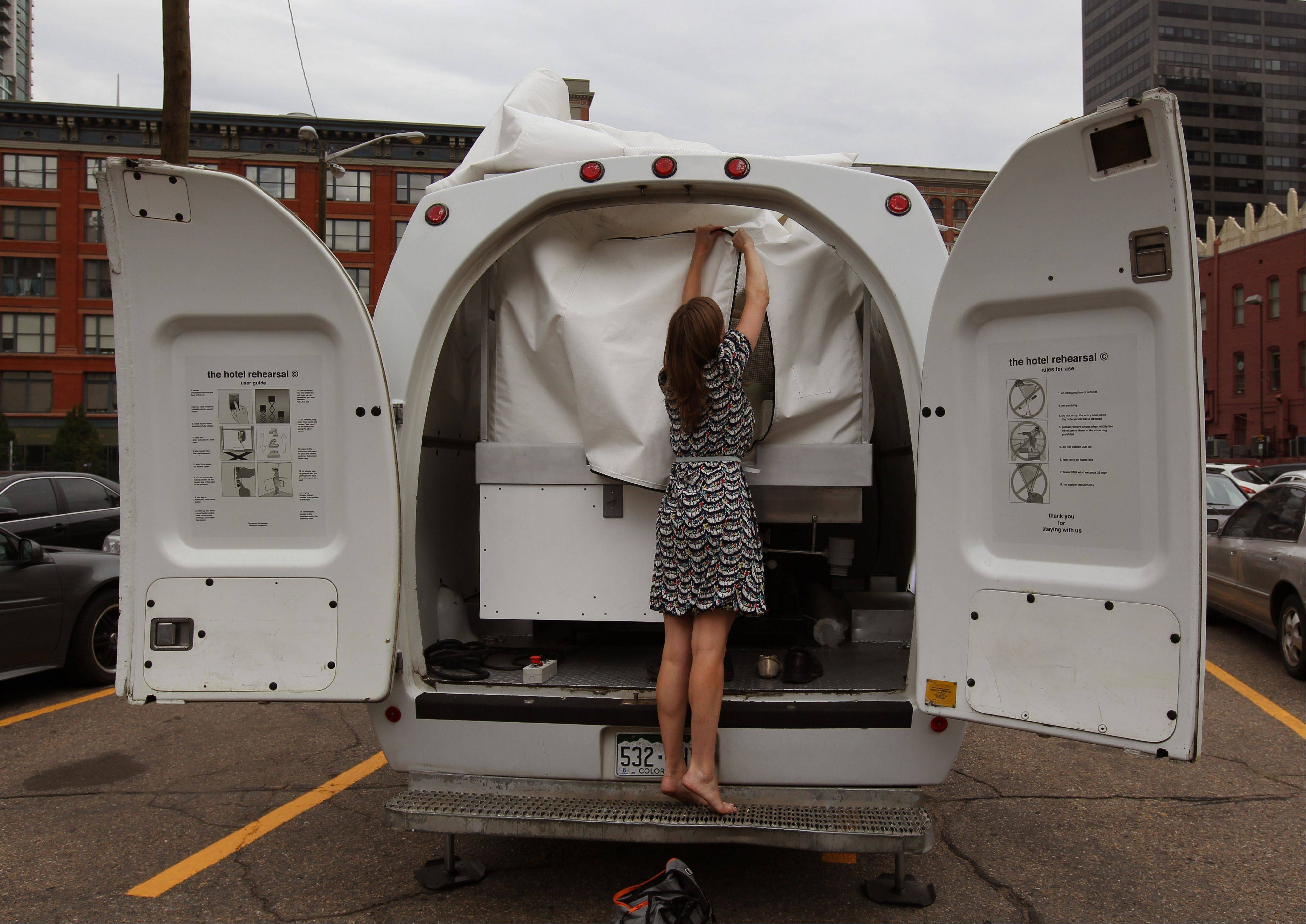 Amelia Langer, an assistant curator of Draft Urbanism, the art exhibition of the 2013 Biennial of the Americas, unzips the opening to a hotel room made of aluminum and inflated vinyl capable of being held aloft by a van-mounted scissor lift during a promotional display in a parking lot in downtown Denver.