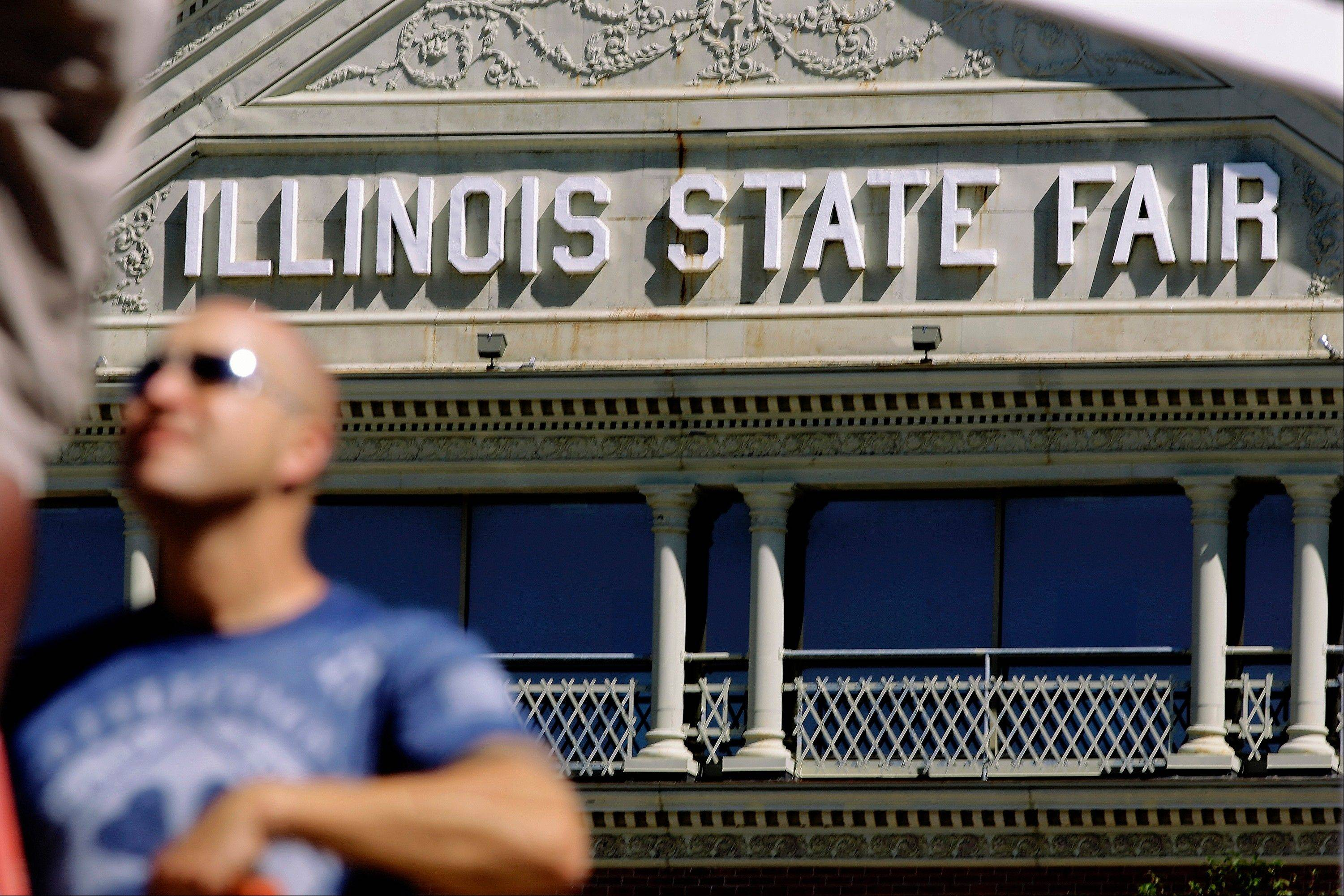 Contractor Bryon Tobin works on installing the Happy Hollow entrance sign at the Illinois State Fairgrounds Thursday in Springfield. The fair begins Aug. 8.