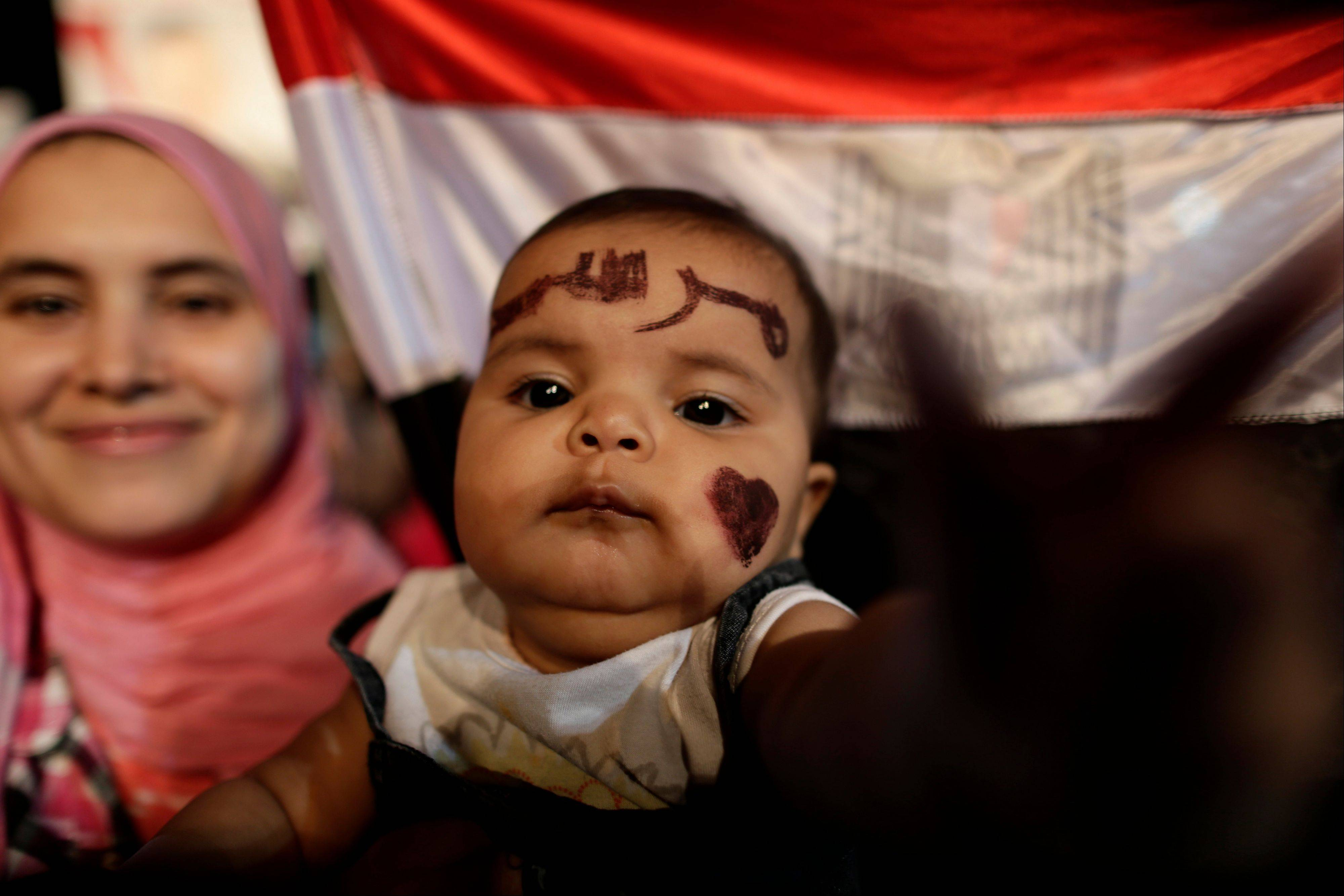 "Qurbah, six months old, with Arabic that reads, ""Morsi,"" painted on her face, attends a demonstration with her mother outside Rabaah al-Adawiya mosque, where they have installed a camp and hold daily rallies at Nasr City, in Cairo, Egypt, Wednesday, July 31, 2013. Egypt's military-backed government has ordered the police to break up the sit-in protests by supporters of ousted President Mohammed Morsi, saying they pose an ""unacceptable threat"" to national security. Egyptian authorities on Thursday offered ""safe passage and protection"" for thousands of supporters of the country's ousted president if they end their marathon sit-ins in Cairo."