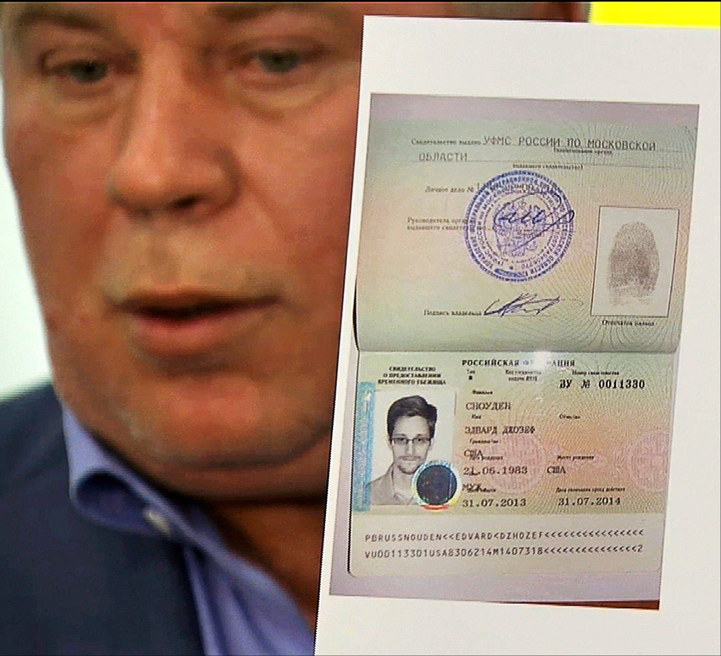 In this image taken from Associated Press Television shows, Russian lawyer Anatoly Kucherena showing a temporary document to allow National Security Agency leaker Edward Snowden to cross the border into Russia at Sheremetyevo airport outside Moscow, Russia, on Thursday, Aug. 1, 2013. National Security Agency leaker Edward Snowden has received asylum in Russia for one year and left the transit zone of Moscow's airport, his lawyer said Thursday.