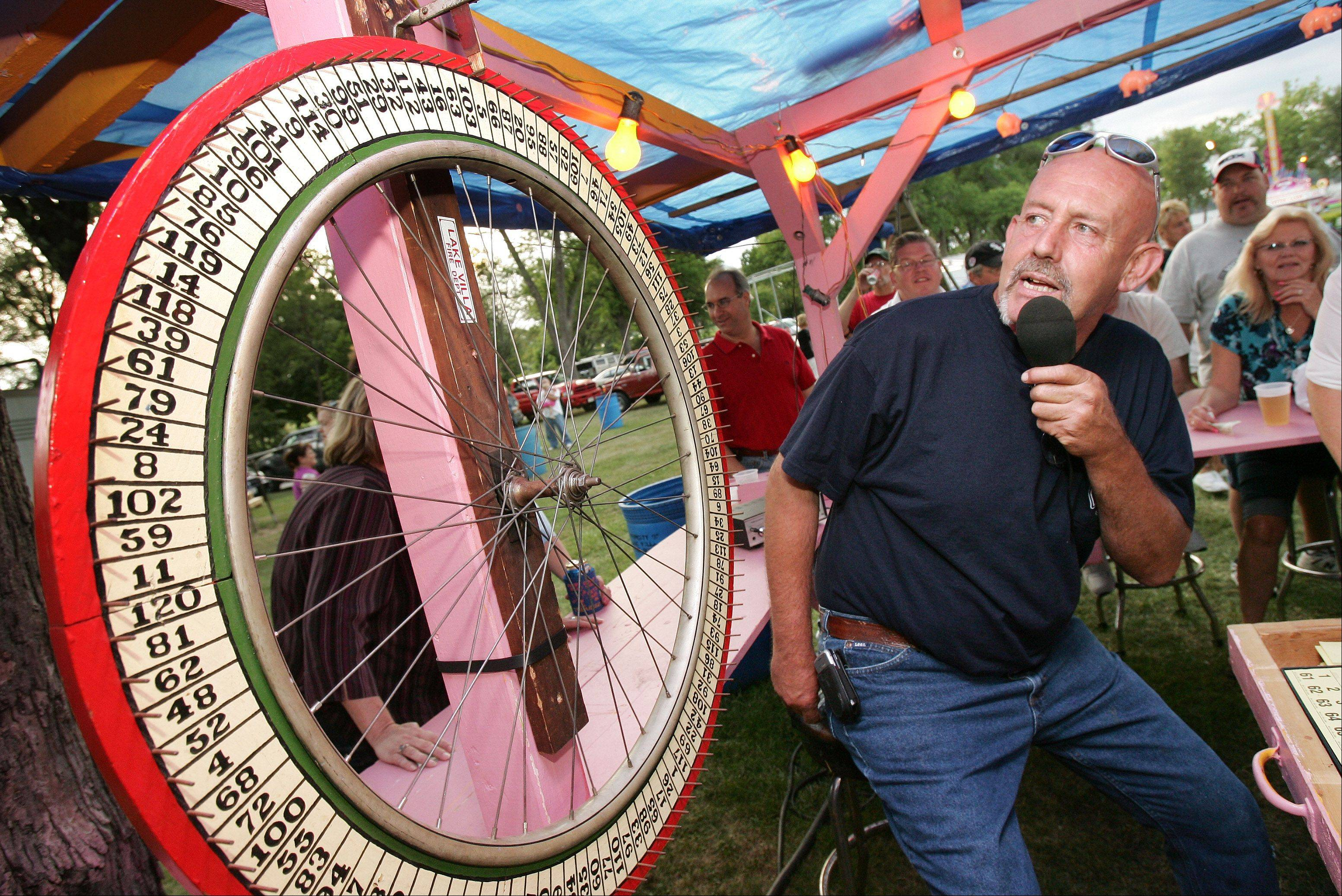 Jim Aronson spins the Wheel of Meat at the Ham and Bacon Stand during the 2009 Lake Villa Days in Lehmann Park.