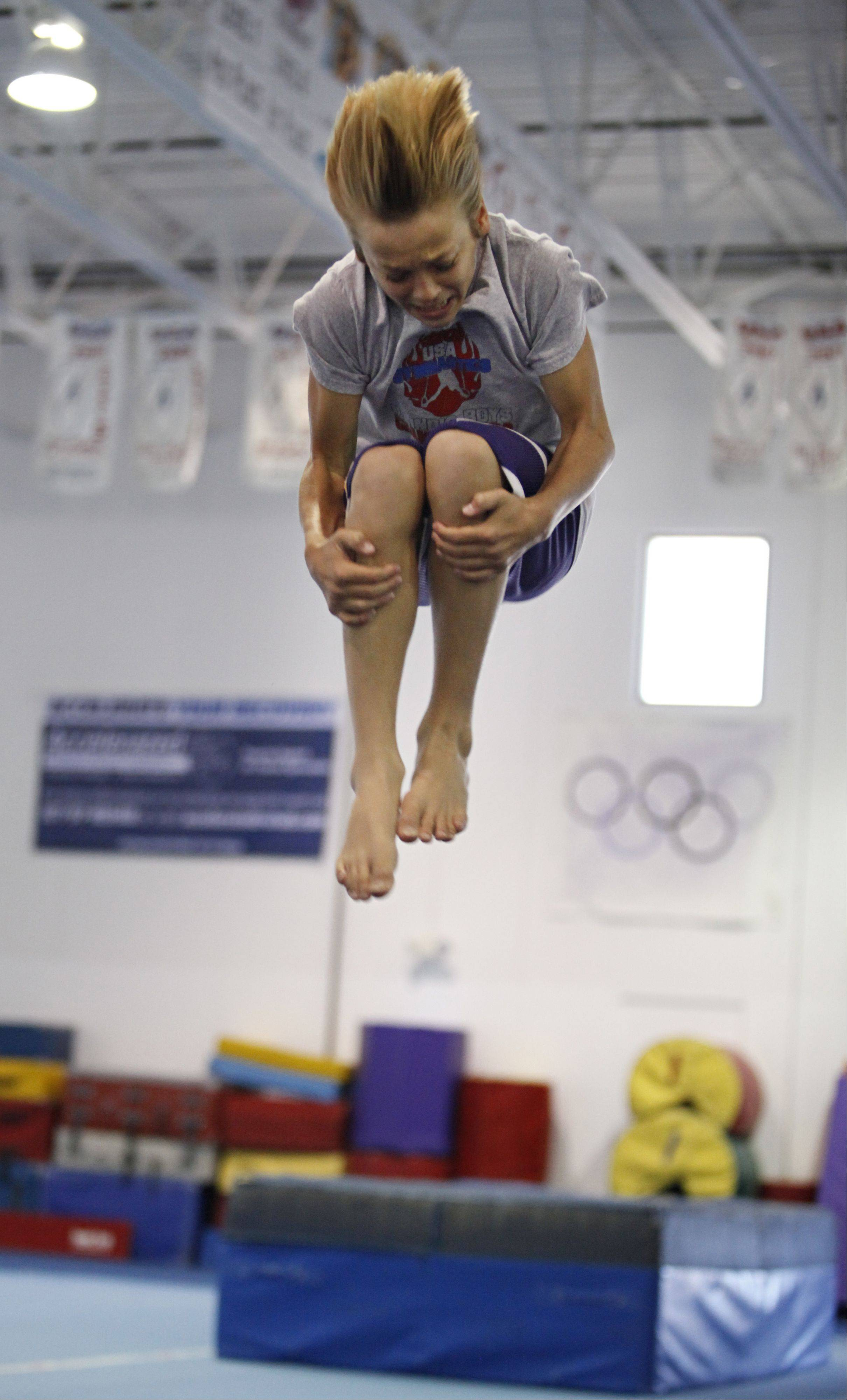 Austin Jones of St. Charles spins through the air in a tuck at the St. Charles Gymnastics Academy. He took the gold medal in the vault and placed 5th in the parallel bars in his age and level at the 2013 Junior Olympic Championships in Portland, Ore.