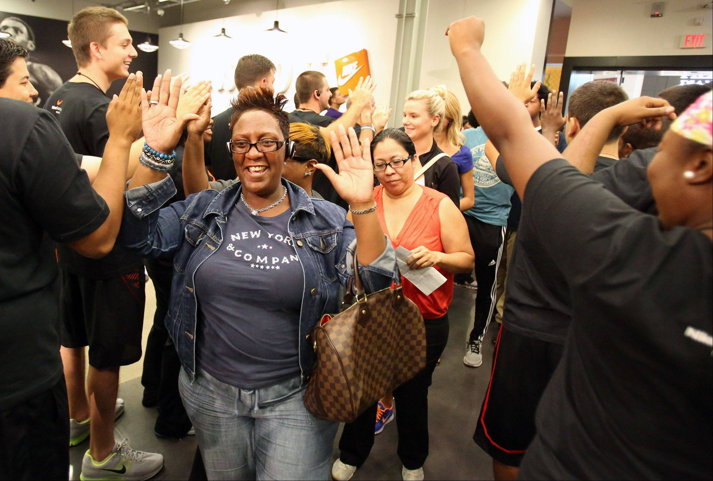 About 75 shoppers who were lined up in front of The Nike Store enter with high-fives by store employees for its grand opening at the Fashion Outlets of Chicago on Thursday.