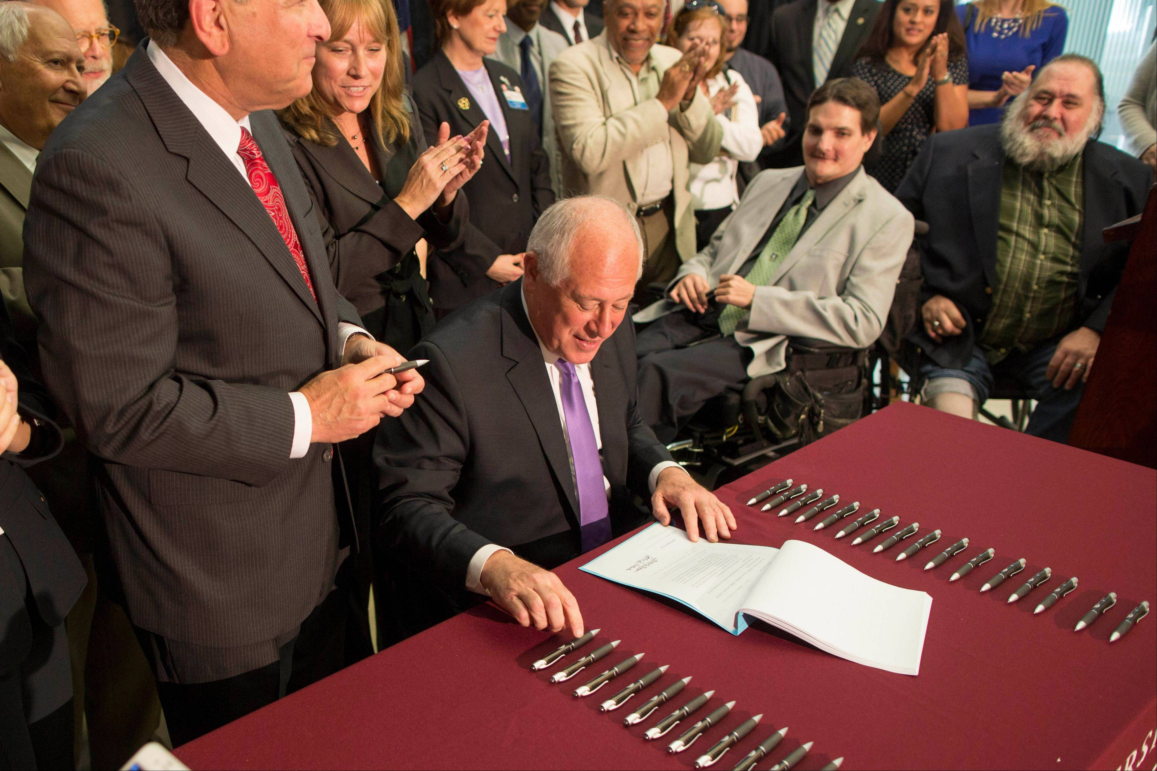 Gov. Pat Quinn signs a bill for medical marijuana Thursday at the University of Chicago Center for Care and Discovery. Patients will be allowed up to 2.5 ounces at a time.