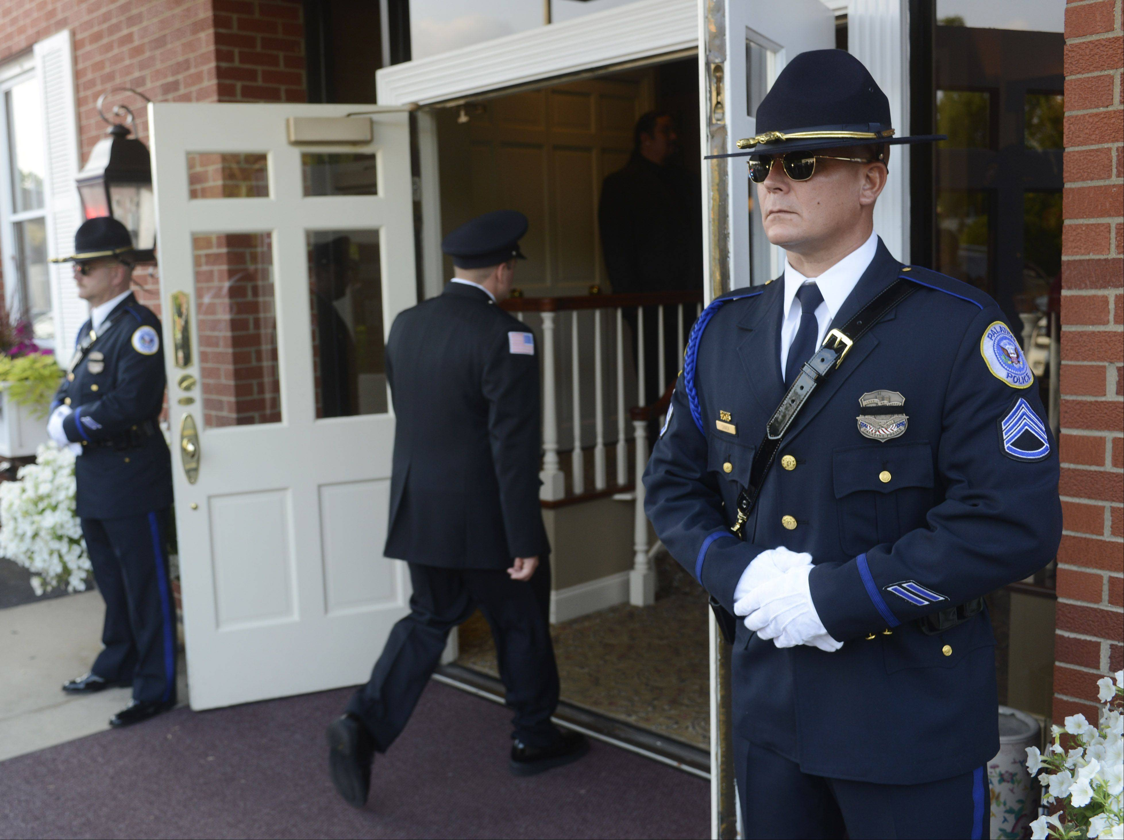Palatine Police Department Sgt. Larry Canada, right, and officer Mark Dockendorf stand at attention outside the entrance during the wake for Wheeling police officer Shamekia Goodwin-Badger at Kosssak Funeral Home in Wheeling last night.