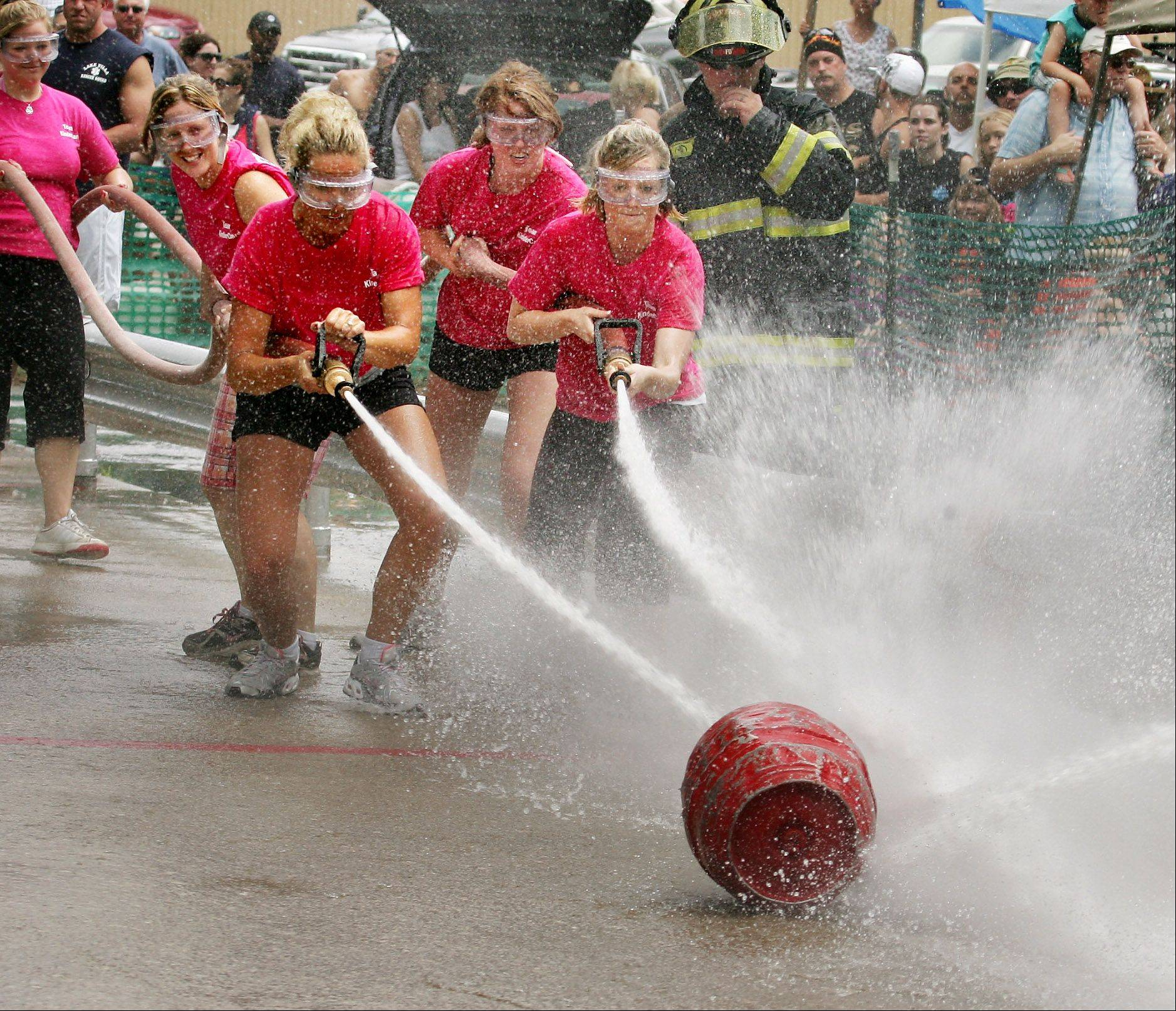 Ashley Ovaska, left, and Jennifer Robinson lead the KinderCare team against the Great American Tire team during the fireman's water fights on the last day of the 2009 Lake Villa Days.