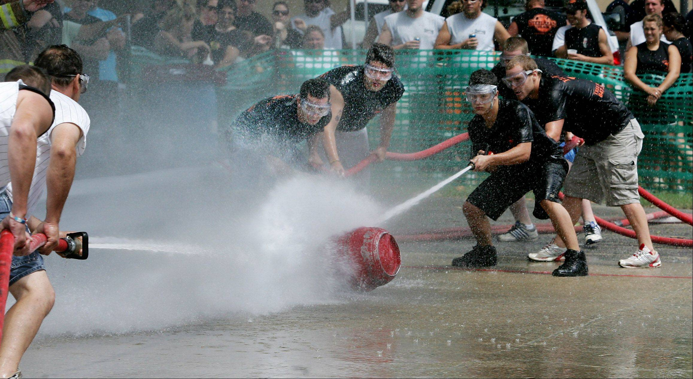 Steve Ziegler, left, and Adam Linczmaier lead the rest of the Horn's Tree Specialist team during the water fights at the 2010 Lake Villa Days.