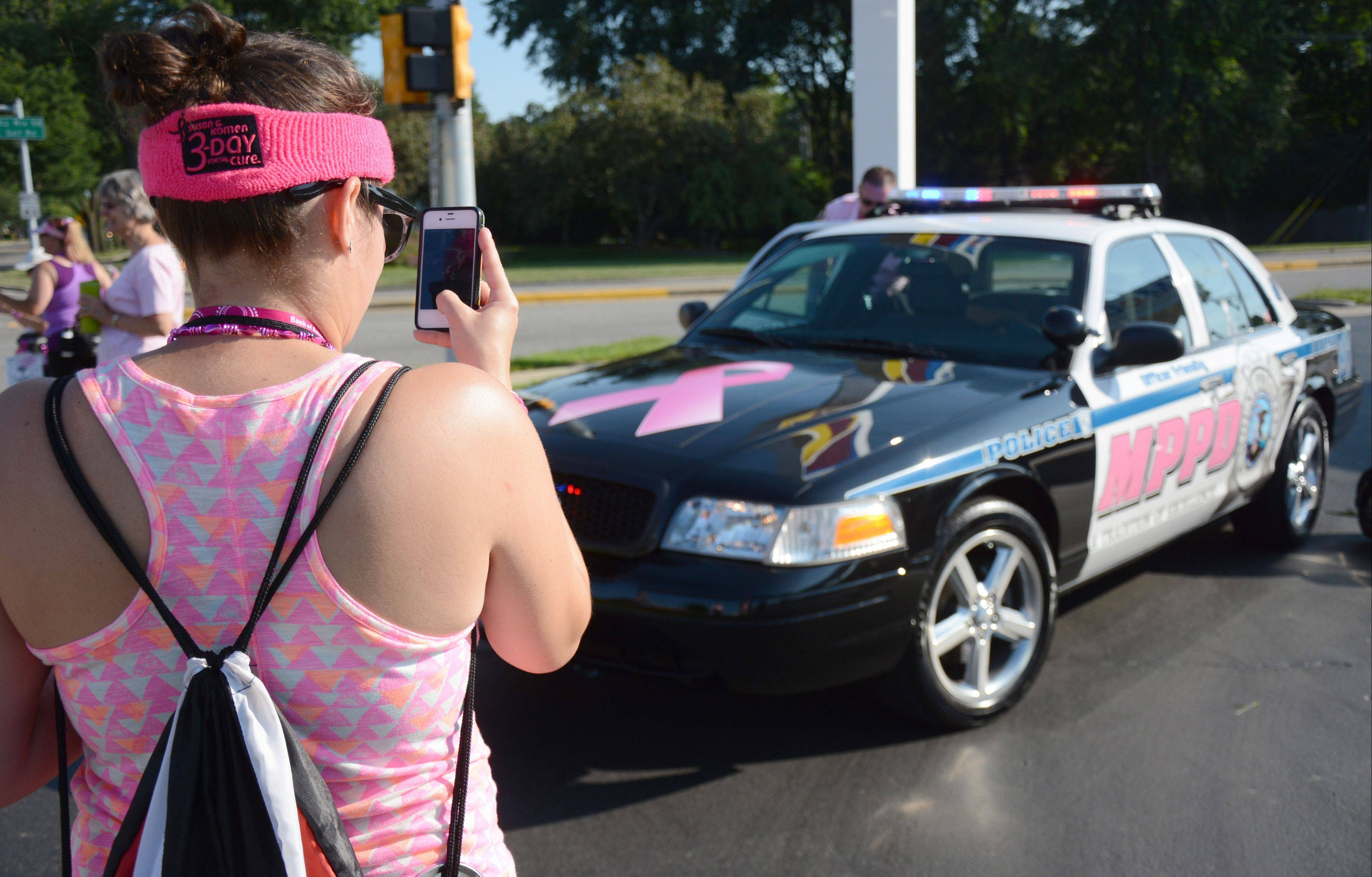 Rebecca Vasques, of Elmhurst, pauses to shoot a picture of a Mount Prospect police cruiser that was decked out in pink Saturday during the second day of the Chicago Breast Cancer Komen 3-Day Walk in Mount Prospect. Vasquez is walking for her mother, a breast cancer survivor.