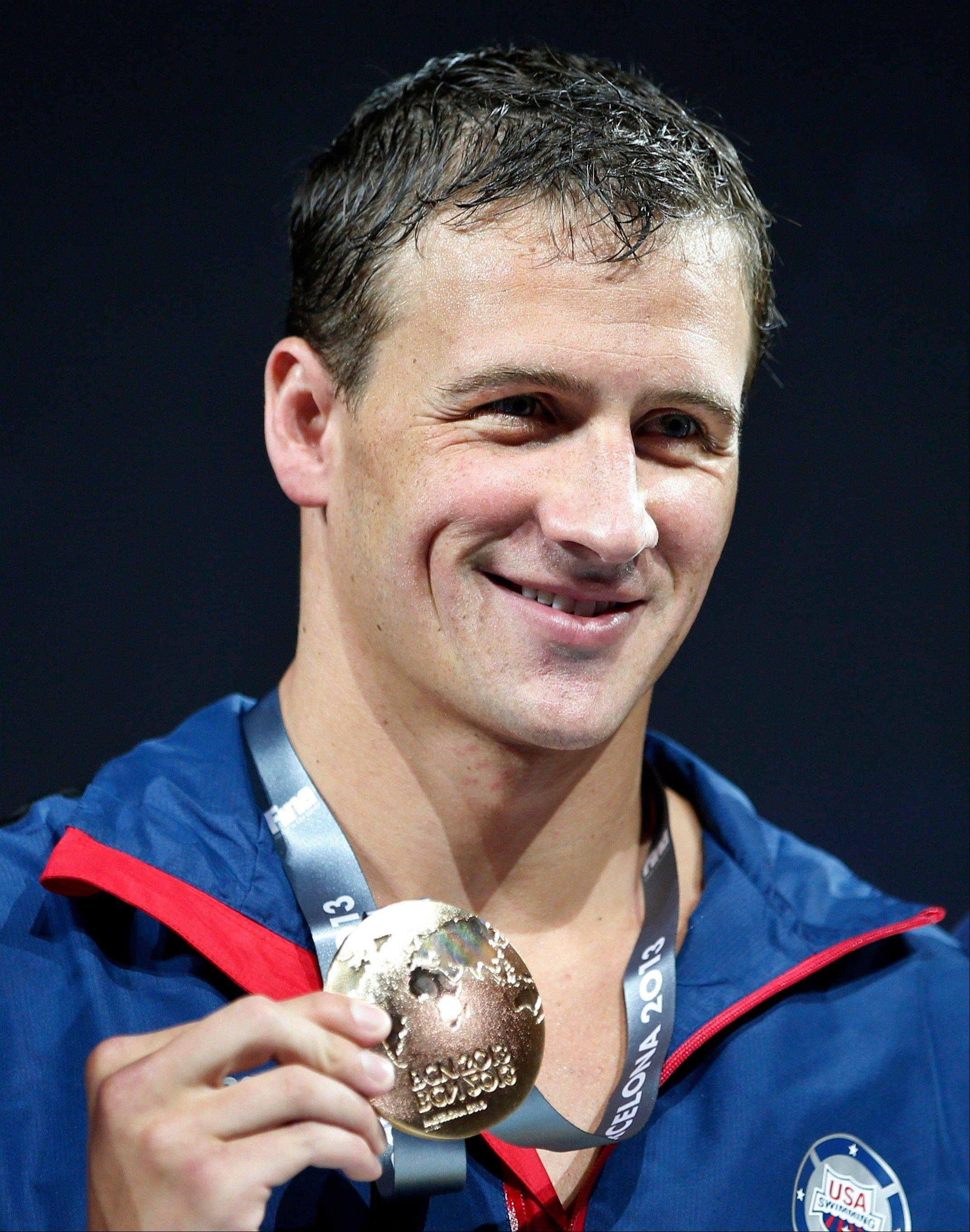 Ryan Lochte of the United States smiles as he holds the gold medal he won in the Men's 200m individual medley final at the FINA Swimming World Championships in Barcelona, Spain, Thursday, Aug. 1, 2013.