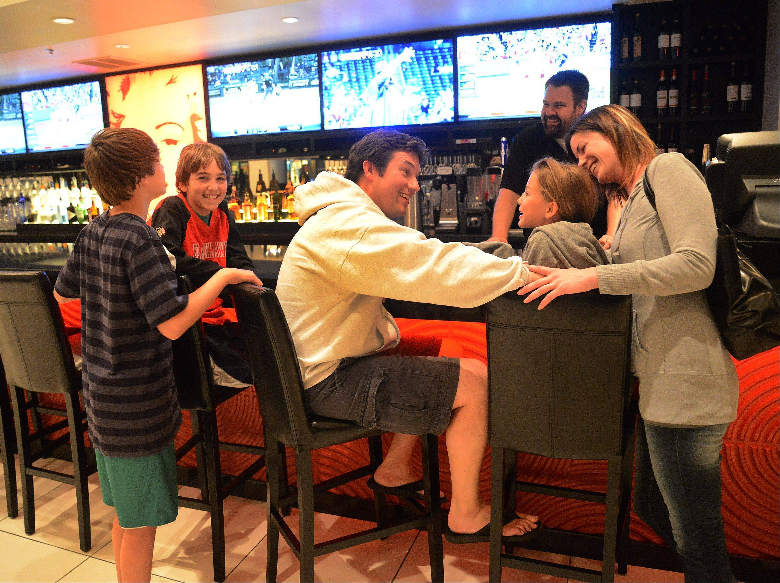 Burke, left, Cole, Jason, Andrea and Jenna Parent of Arlington Heights enjoy themselves in the lobby after a movie at the Star Cinema Grill.