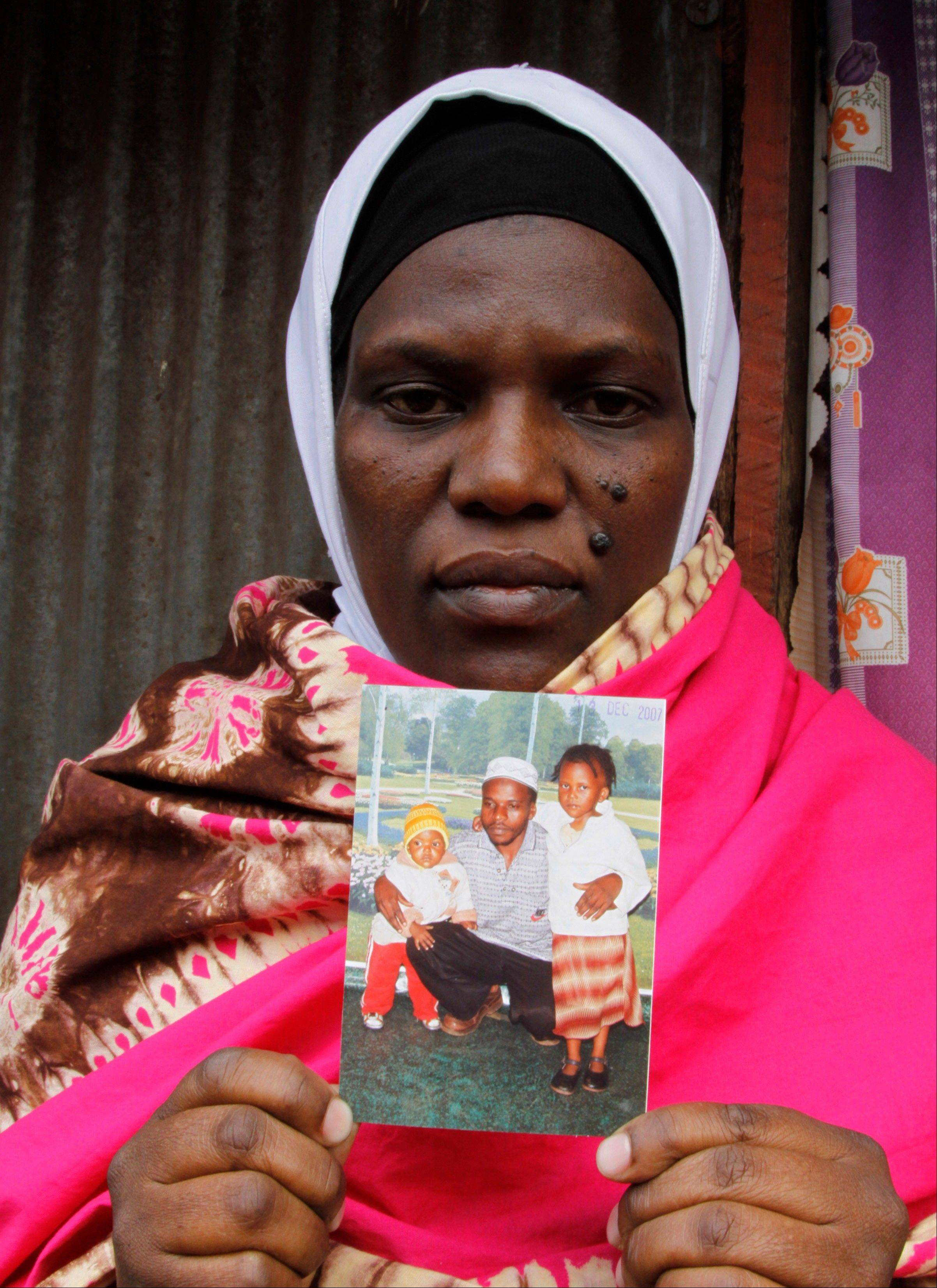 Latifah Naiman Mariki, widow of the late Haji Lukindo, holds a family photo Friday showing her late husband and her two daughters outside her house in Nairobi, Kenya.