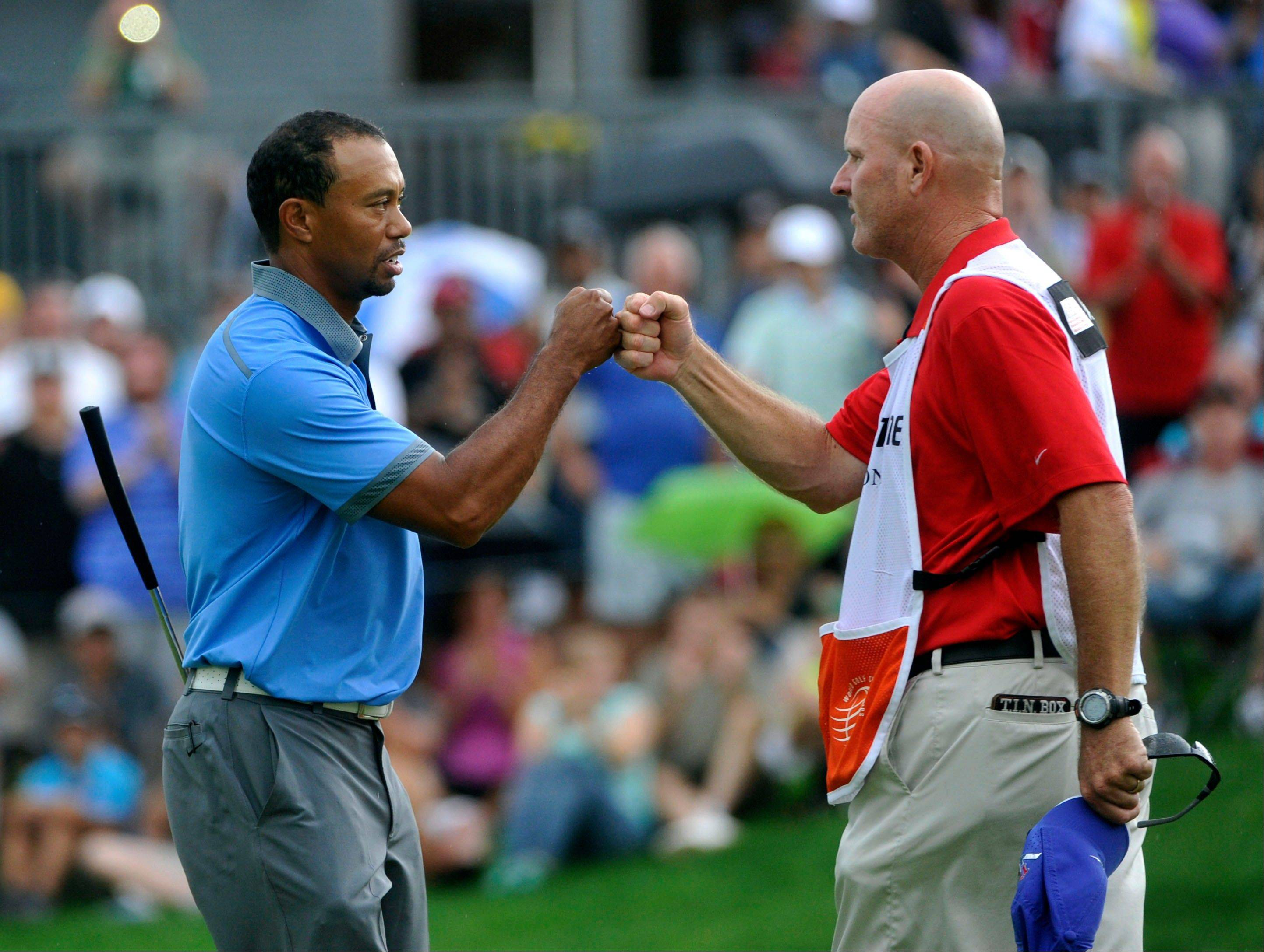 Tiger Woods celebrates with his caddy Joe LaCava after finishing his second round, at the WGC Bridgestone Invitational golf tournament, at Firestone Country Club in Akron, Ohio, Friday, Aug. 2, 2013. Woods shot a nine-under par 61, tying the tournament single-round record. (AP Photo/Phil Long)