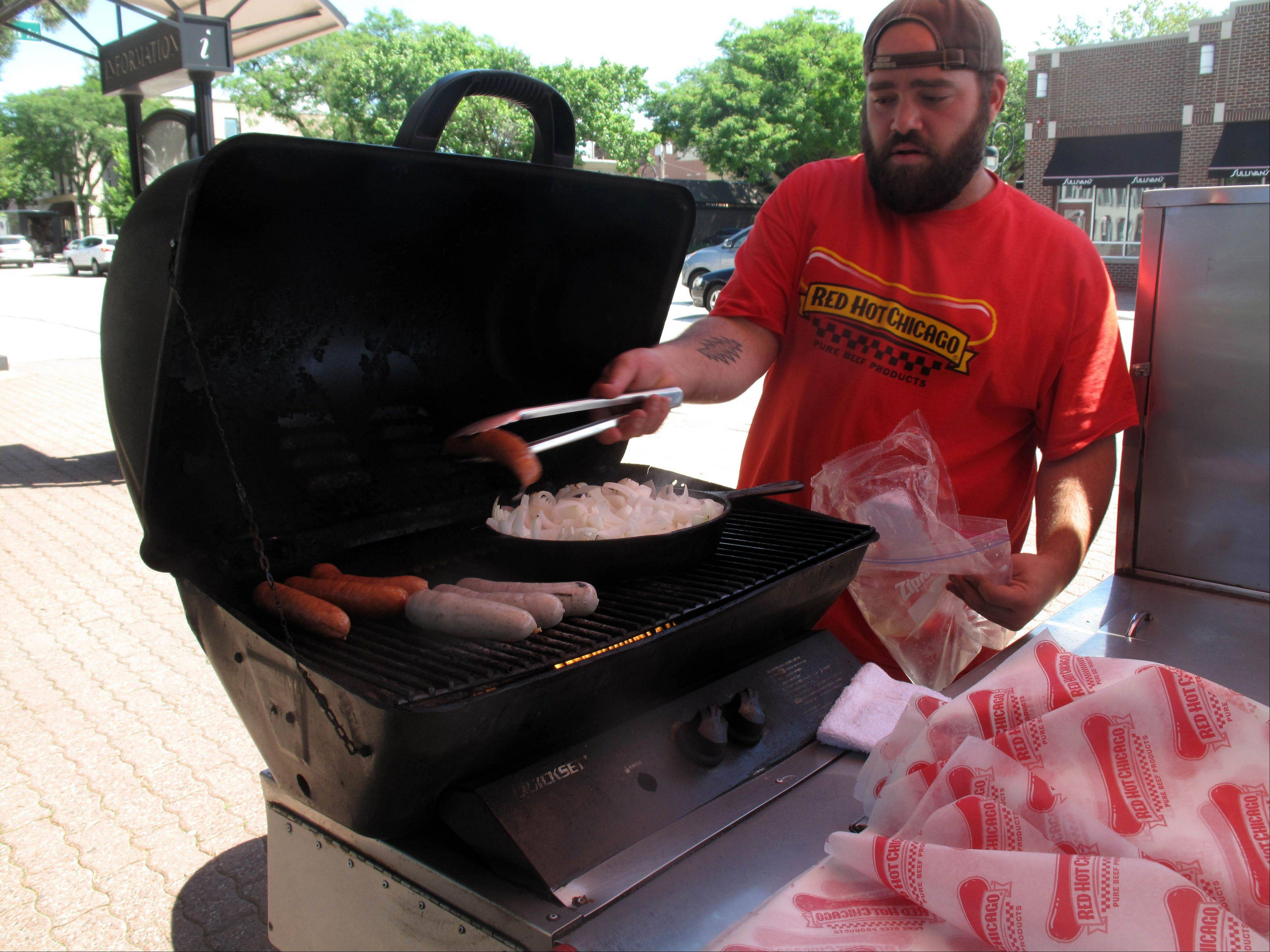 Joe Hornbaker of Joey's Red Hots starts grilling hot dogs, brats and onions from his food cart on Main Street just south of Jackson Avenue near the Riverwalk's horse trough fountain in Naperville. The city soon will survey the public to gather thoughts on food carts in the downtown.