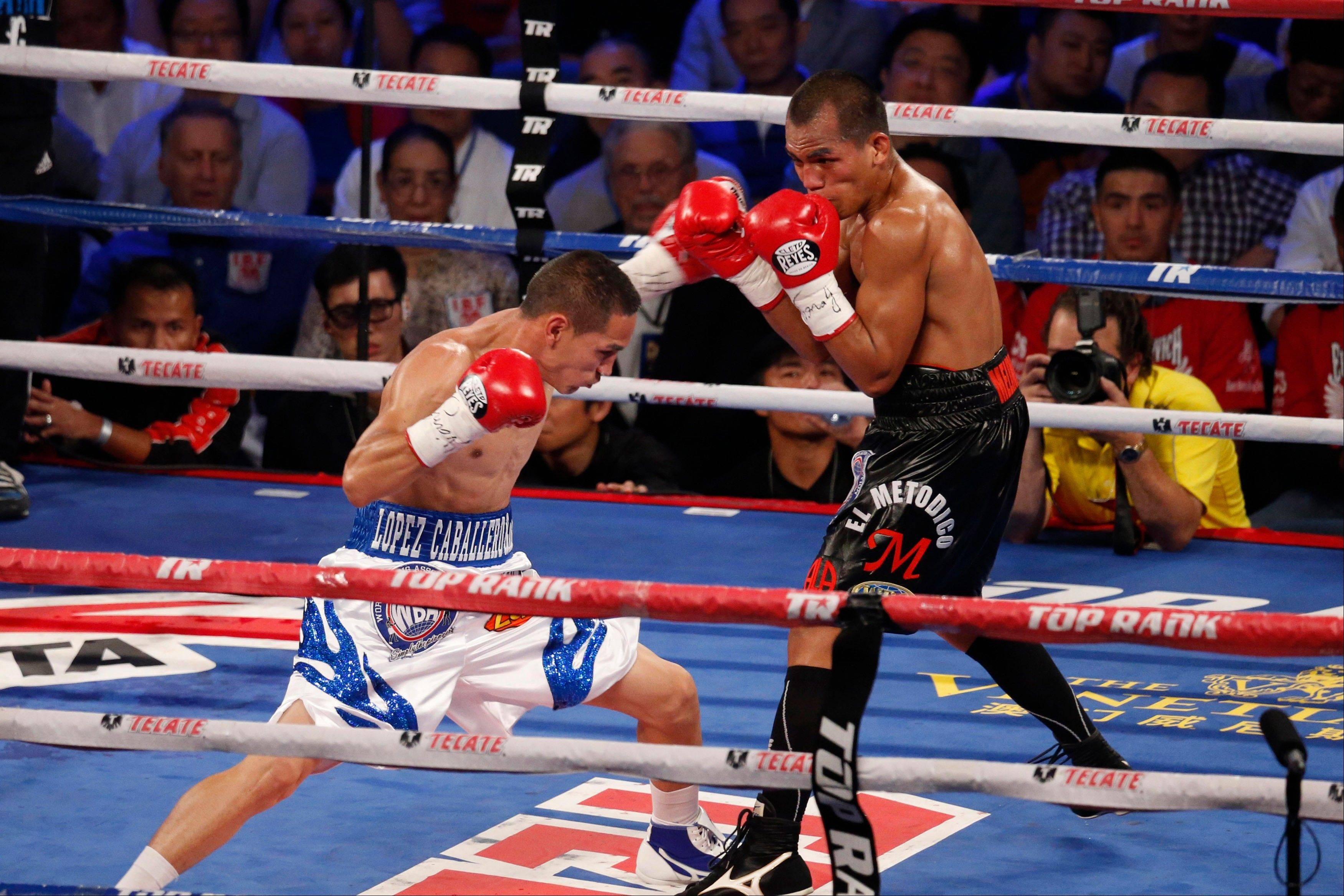 Mexico's Juan Francisco Estrada, left, fights against Milan Melindo of the Philippines during their WBO/WBA Flyweight title match at the Cotai Arena in Venetian Macao in Macau.