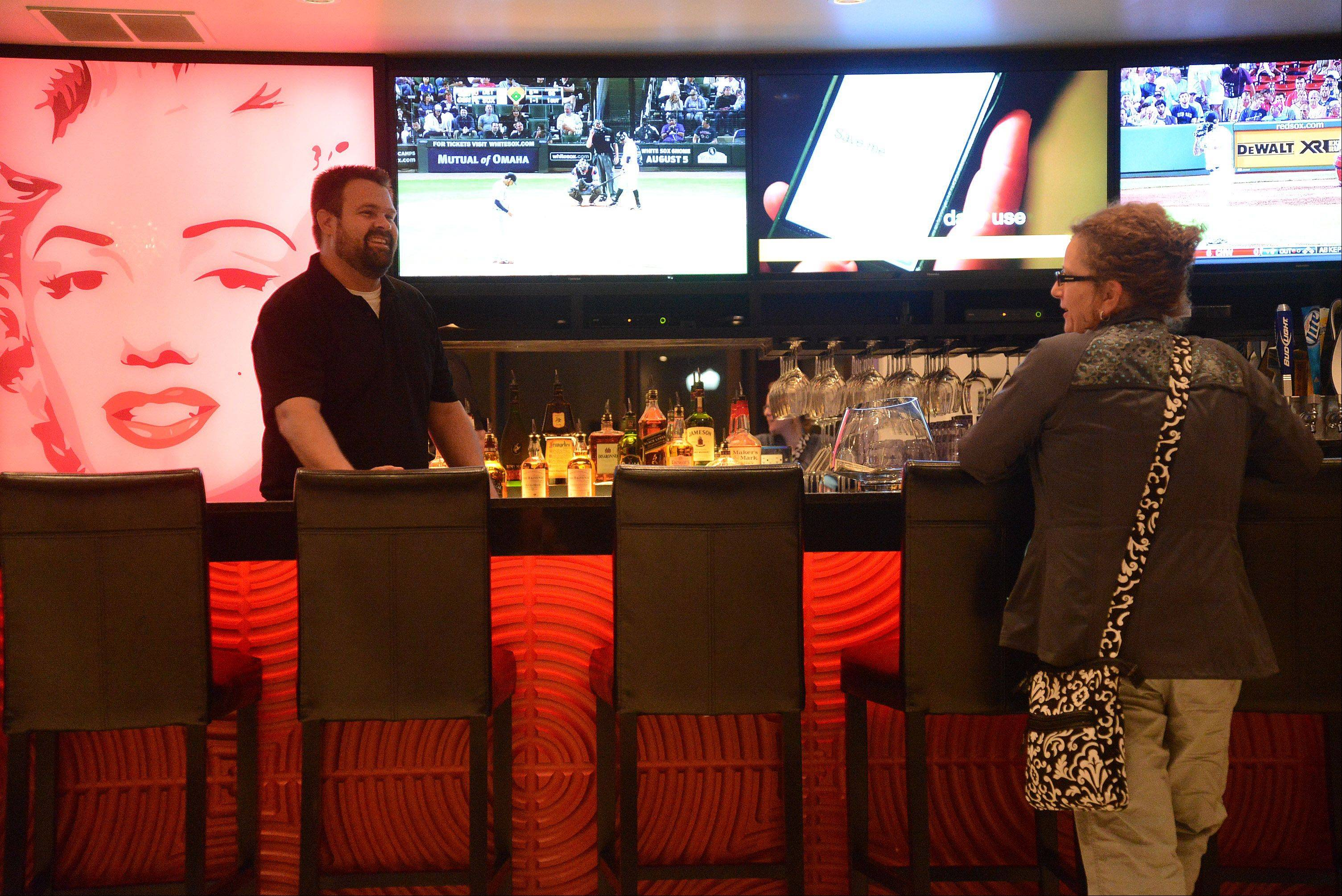 Bartender Bob Strass talks with Kathleen Samuelson of Des Plaines at the new Star Cinema Grill in Arlington Heights.
