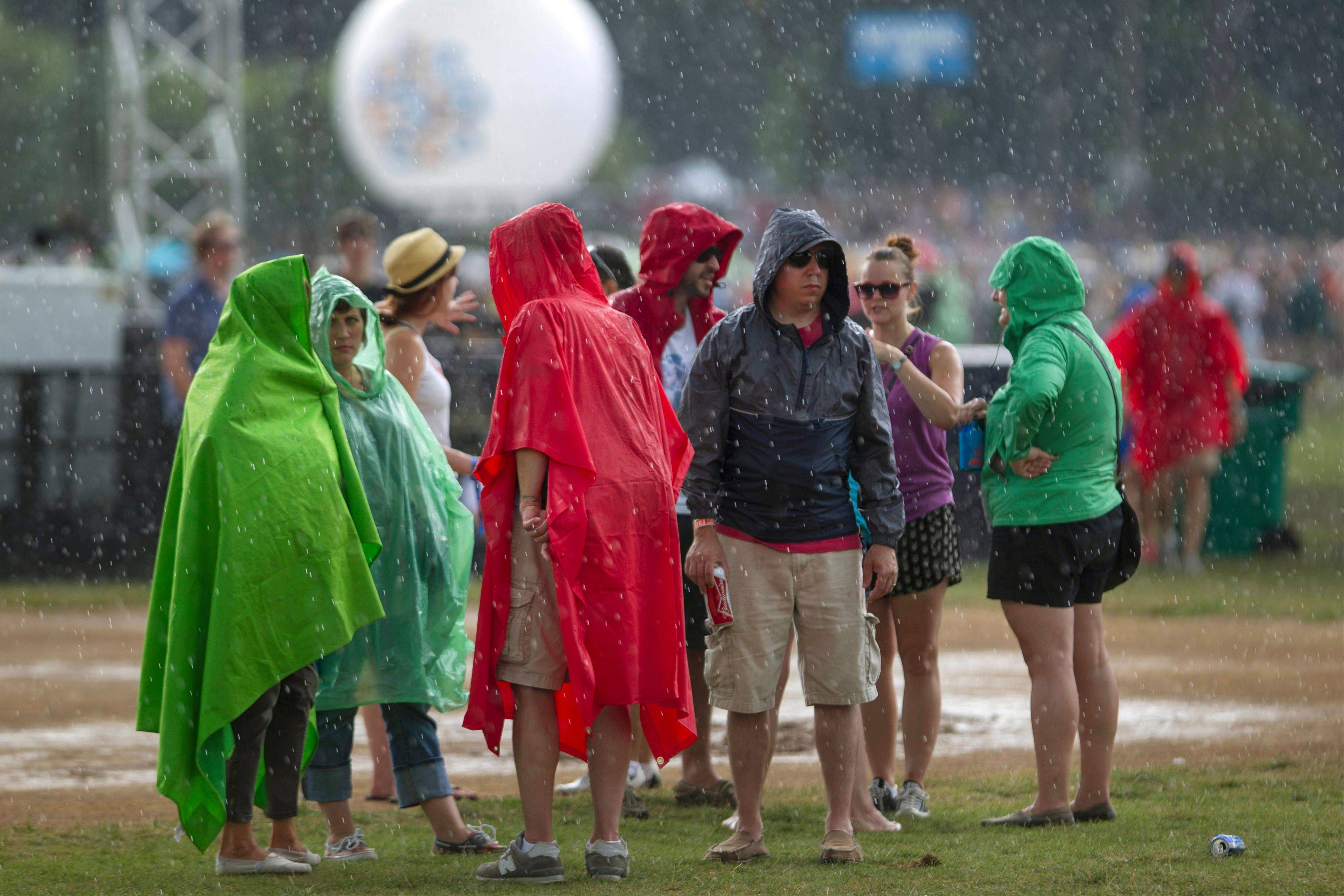Festival attendees stand in ponchos during a brief rain storm at the Lollapalooza Festival in Chicago, Friday, Aug. 2, 2013. The more than two-decade-old festival opens Friday in Chicago's lakefront Grant Park.