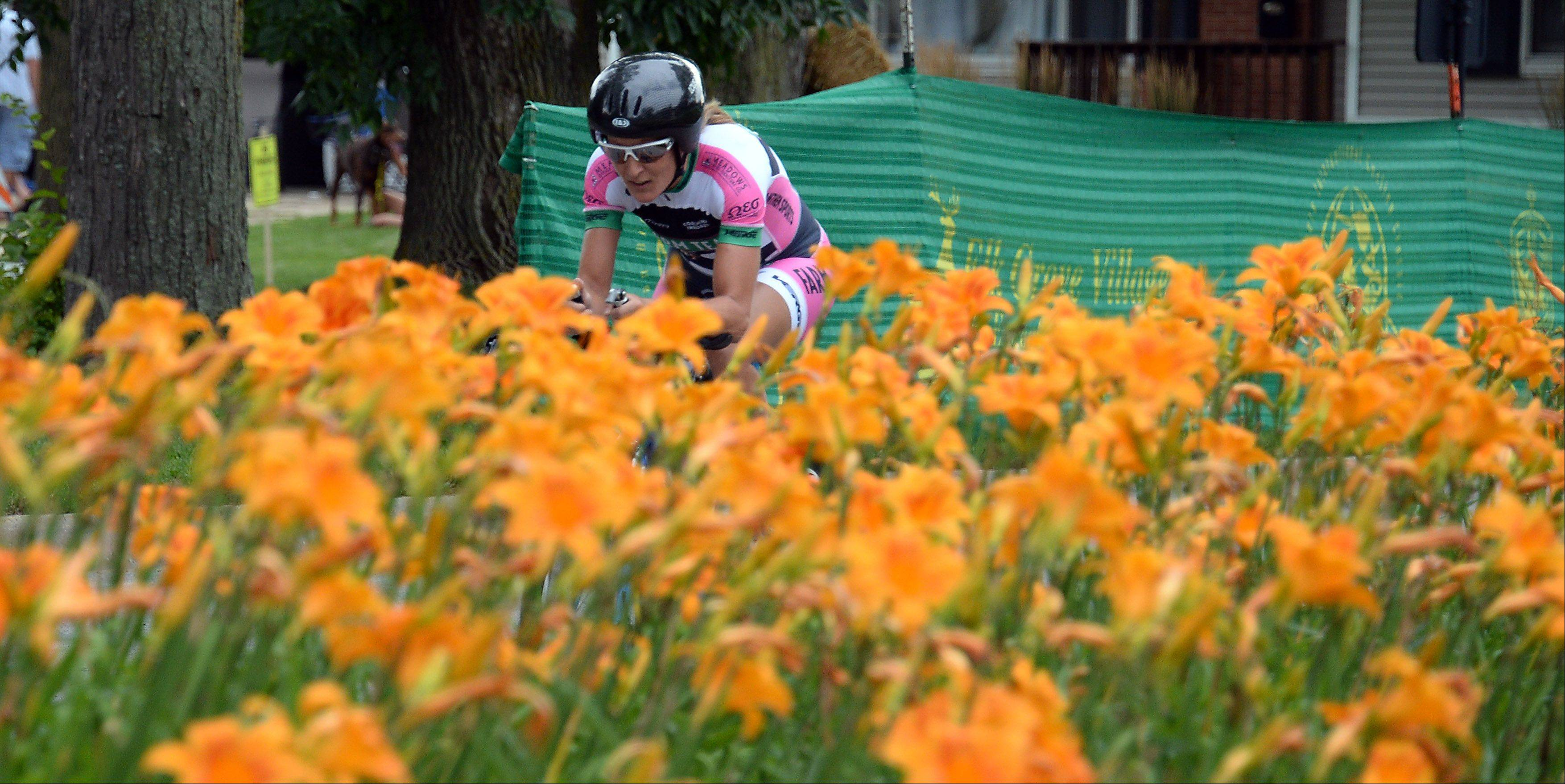 A woman biker rides past a field of flowers as she heads towards the finish line in the 2013 Alexian Brothers Tour of Elk Grove Woodfield Chicago Northwest Convention Bureau Pro Women's time trials on day one of the three-day event.