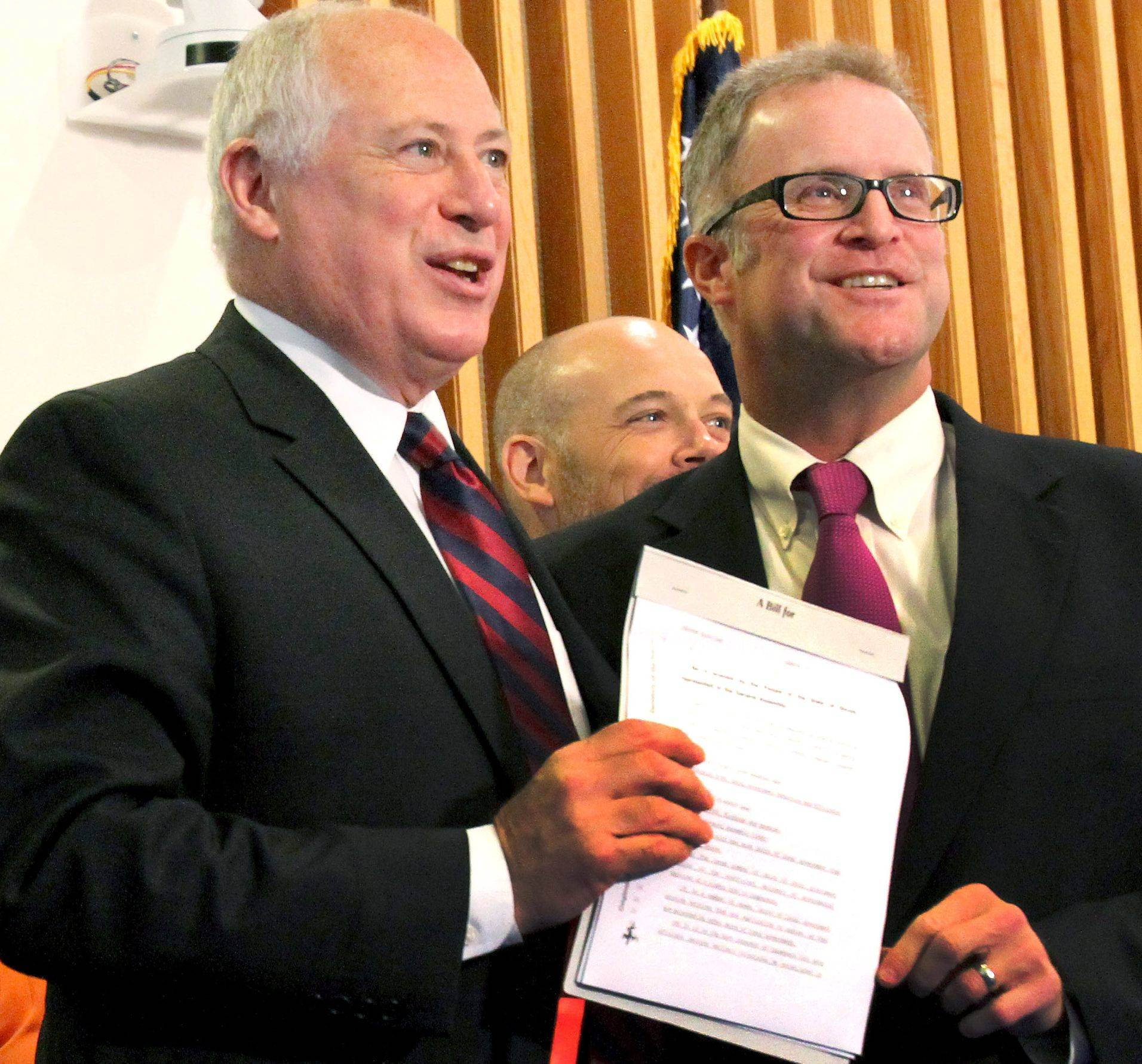 Gov. Pat Quinn and DuPage County Board Chairman Dan Cronin hold up a copy of a new law that lets DuPage eliminate as many as 13 local governmental entities.