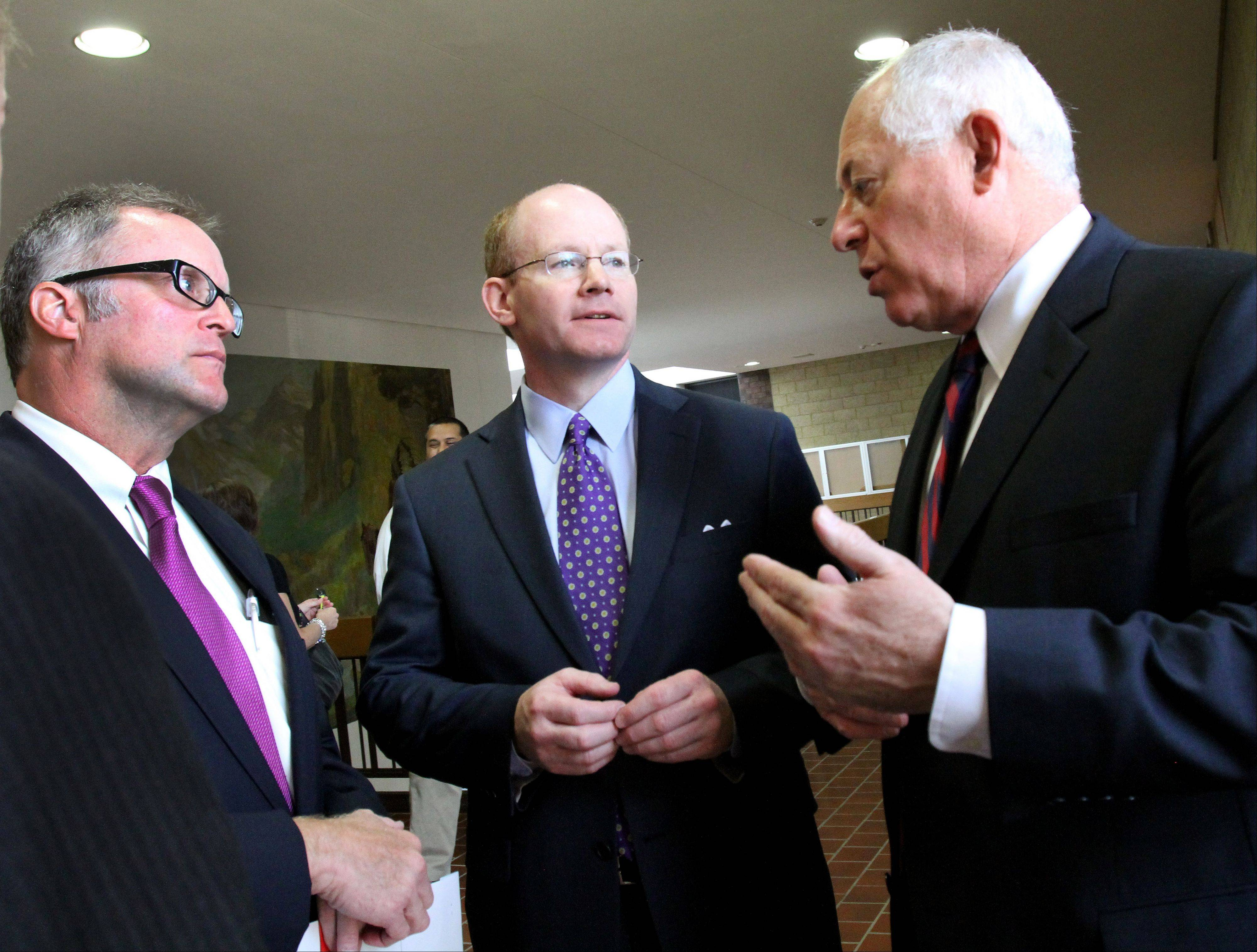 Gov. Pat Quinn speaks with DuPage County Board Chairman Dan Cronin, left, and state Sen. Don Harmon, center, Friday in Wheaton after Quinn signed a new law giving DuPage the authority to eliminate up to 13 local governmental entities.