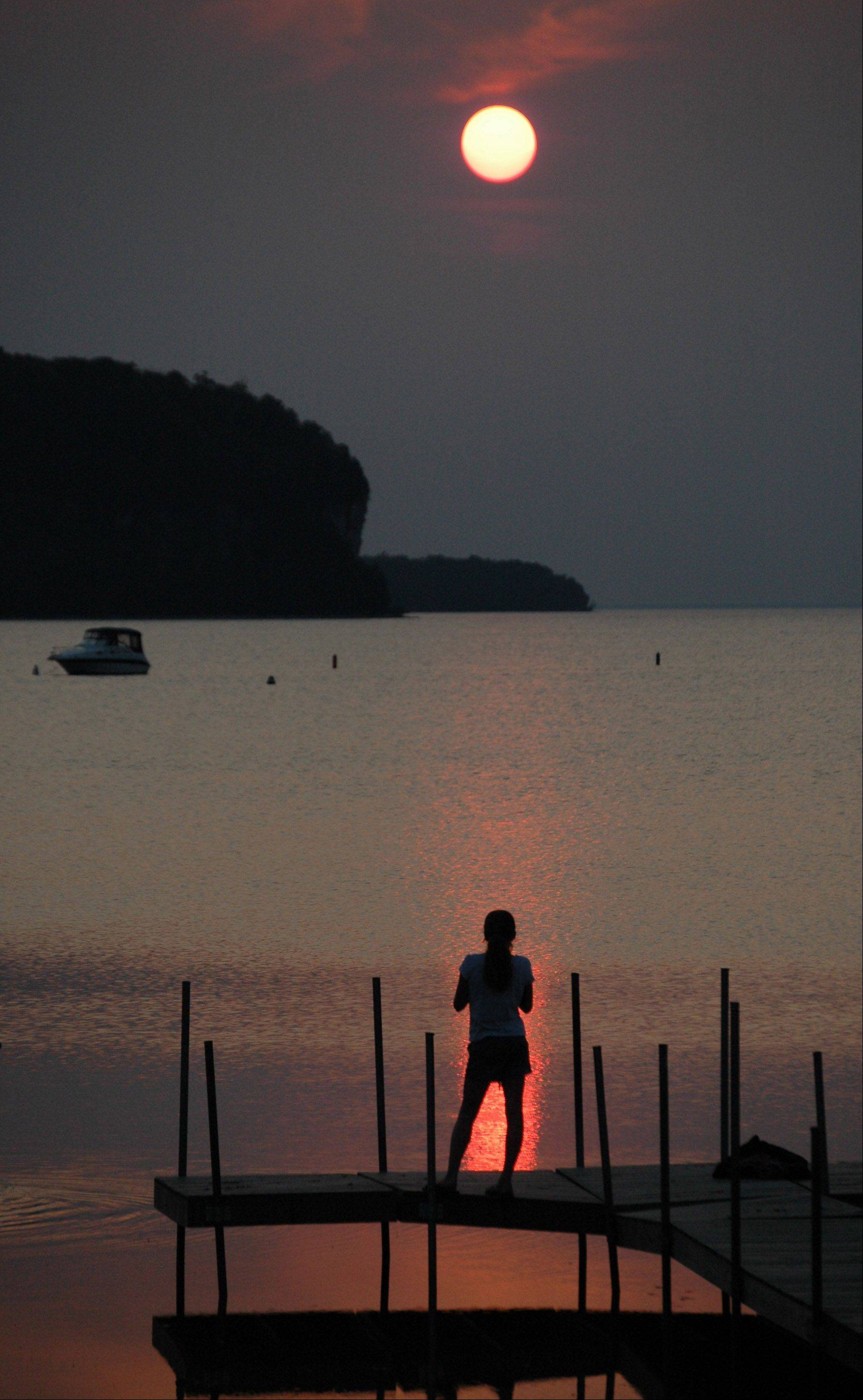While enjoying a summer walk along Eagle Harbor in Ephraim, Wisconsin, we noticed this girl momentarily silhouetted by light from the setting sun as clouds rolled in for the evening.