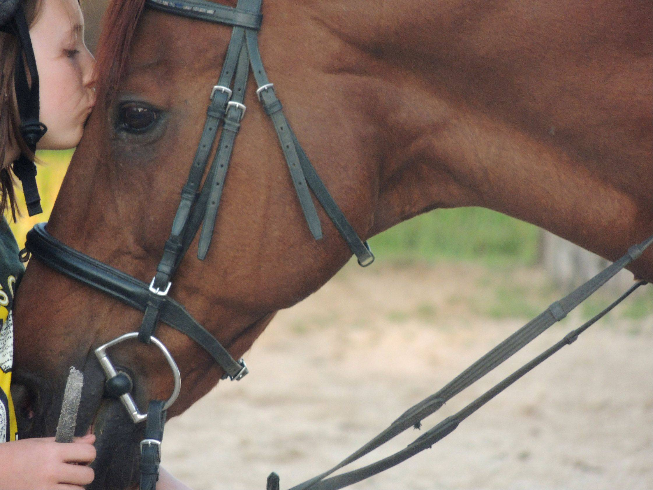 Claire Hess kisses her sisters horse, Acorn, after a riding lesson several months ago in Gilberts.