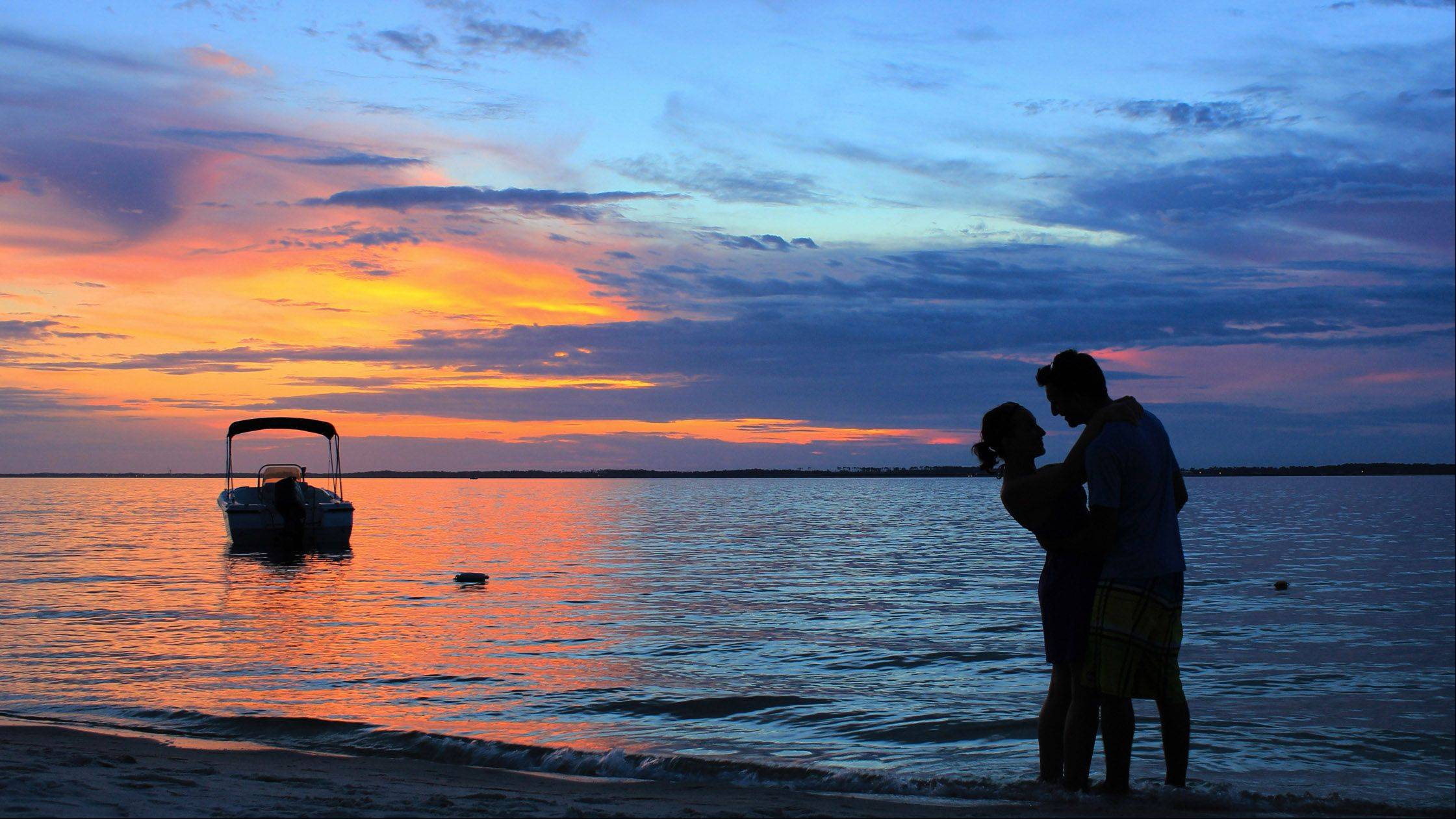 Emily and Giovanni Falco share a romantic moment as the sun sets over the bay in Pensicola, Florida on July 7th.