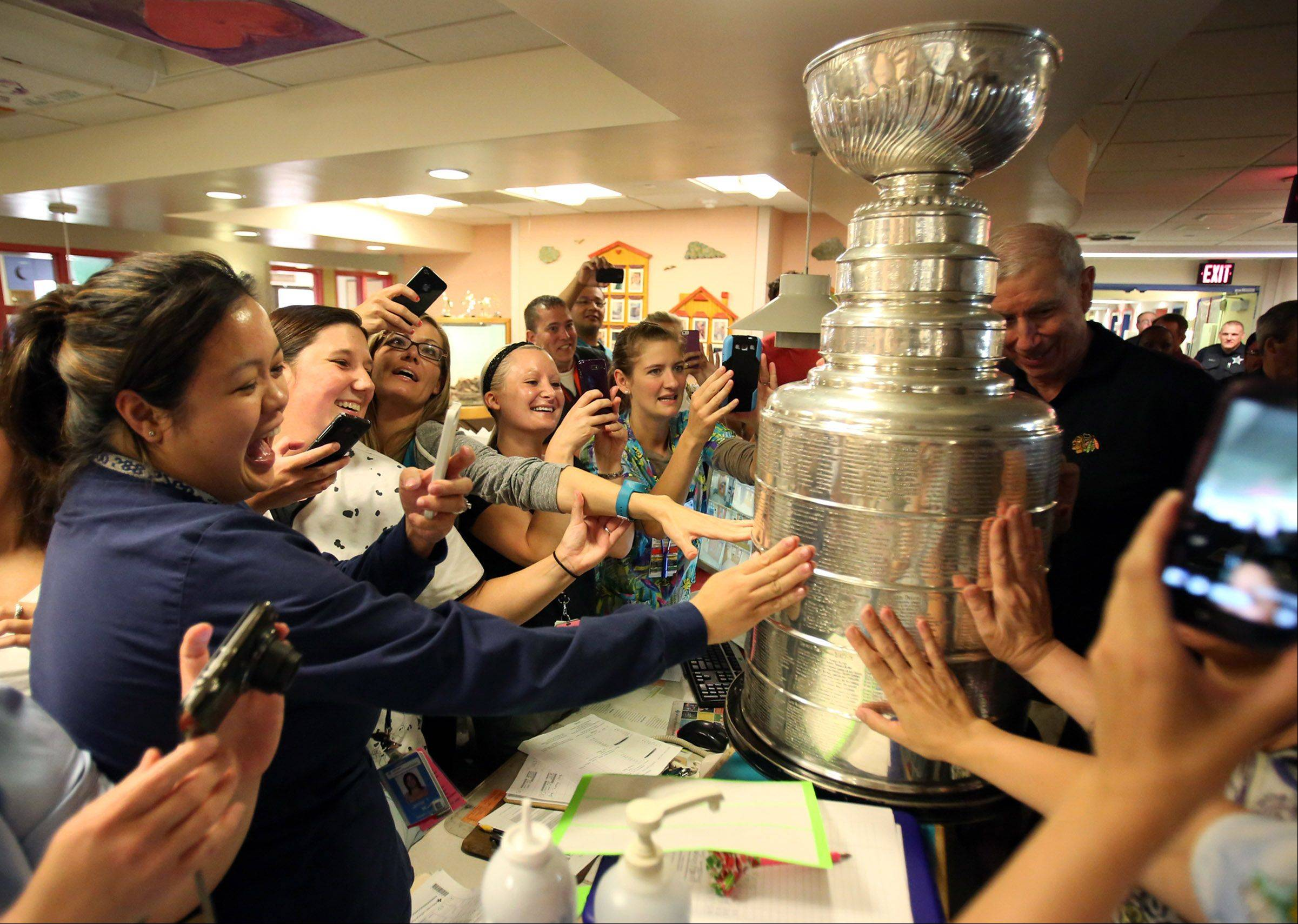 A dozen pediatric nurses took smartphone photos of the Stanley Cup as John McDonough, president and CEO of the Chicago Blackhawks, placed it on the counter of their workstation Saturday at Advocate Children's Hospital in Park Ridge.