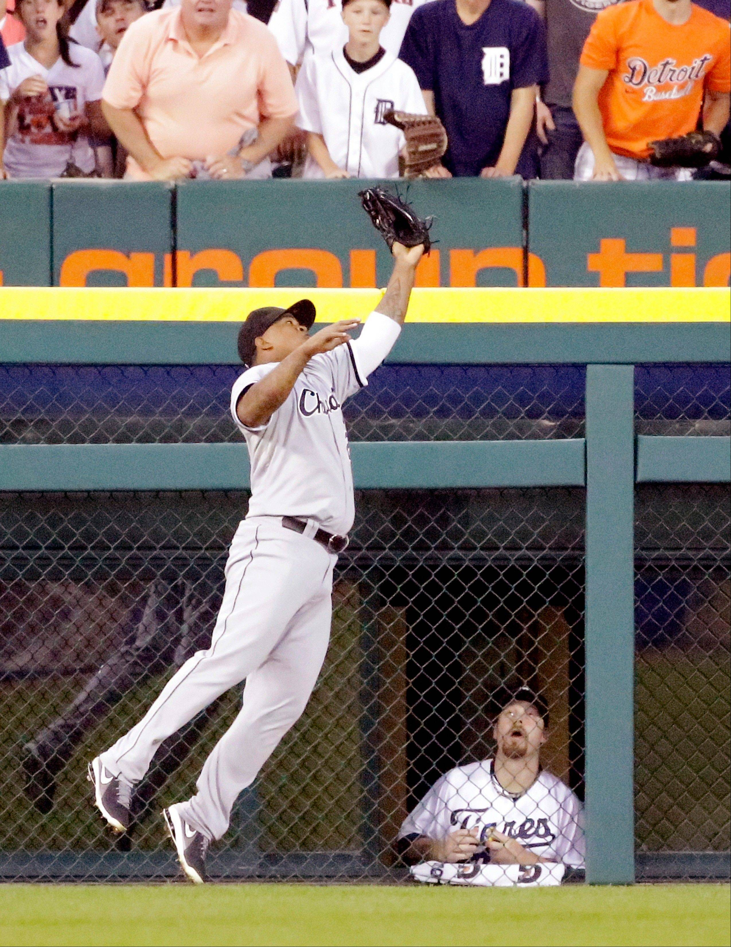 Detroit Tigers relief pitcher Phil Coke, lower right, watches as Chicago White Sox left fielder Dayan Viciedo catches the a long fly ball hit by Tigers designated hitter Victor Martinez during the sixth inning of a baseball game in Detroit, Saturday, Aug. 3, 2013. (AP Photo/Carlos Osorio)