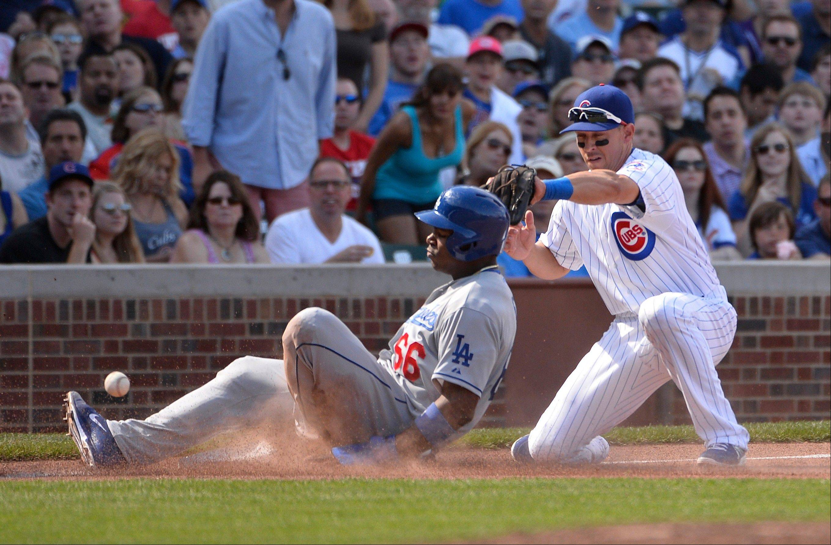 Los Angeles Dodgers' Yasiel Puig, left, slides safely into third base, advancing from first base on a single hit by teammate Andre Ethier, as Chicago Cubs third baseman Cody Ransom tries to make a play during the third inning of a baseball game, Saturday, Aug. 3, 2013, in Chicago. (AP Photo/Brian Kersey)