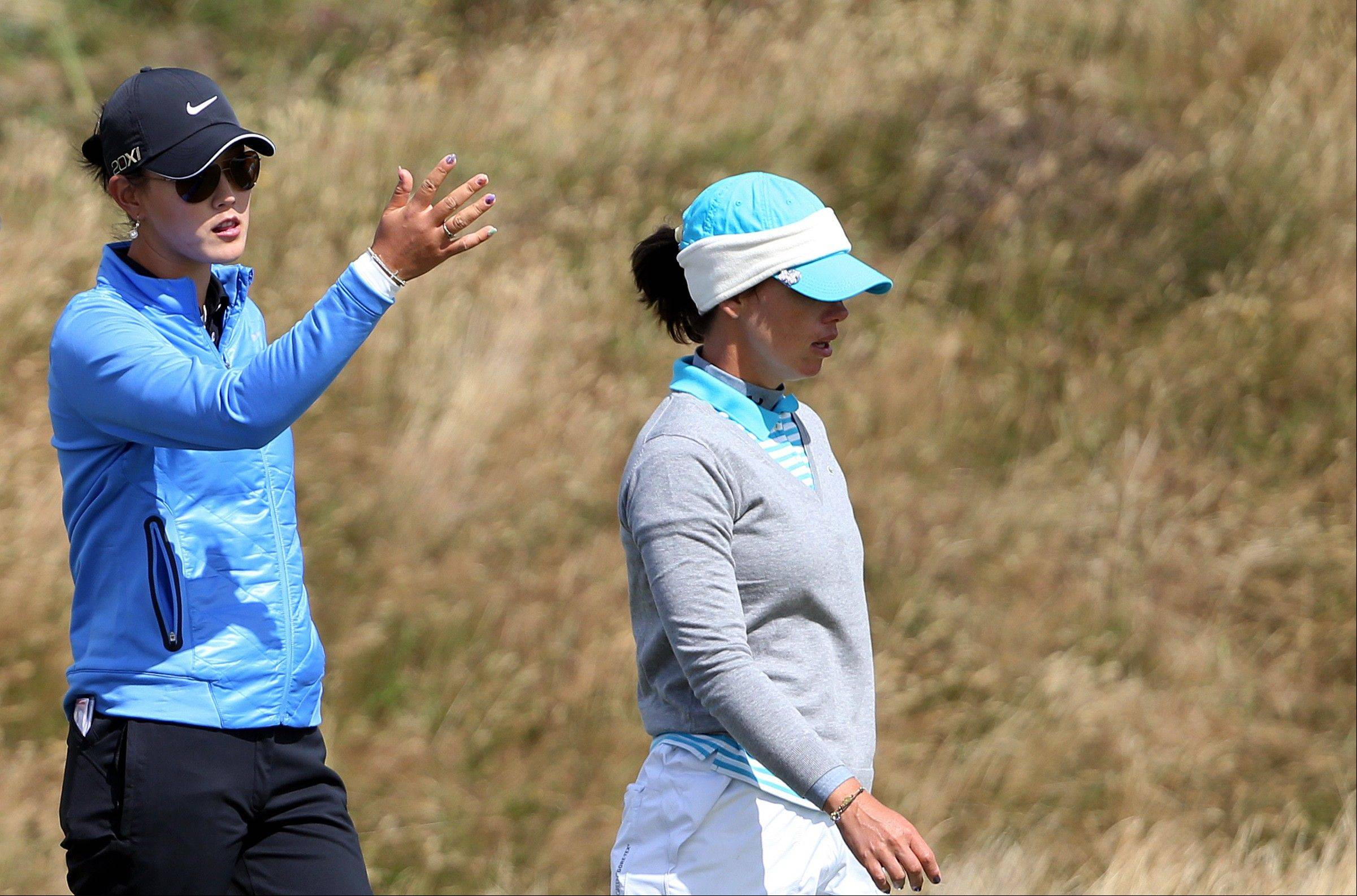 Michelle Wie of the US, left, reacts to France's Karine Icher, right, after play has been suspended due to the high winds on the 13th fairway during the third round of the Women's British Open golf championship on the Old Course at St Andrews, Scotland, Saturday Aug. 3, 2013. (AP Photo/Scott Heppell)