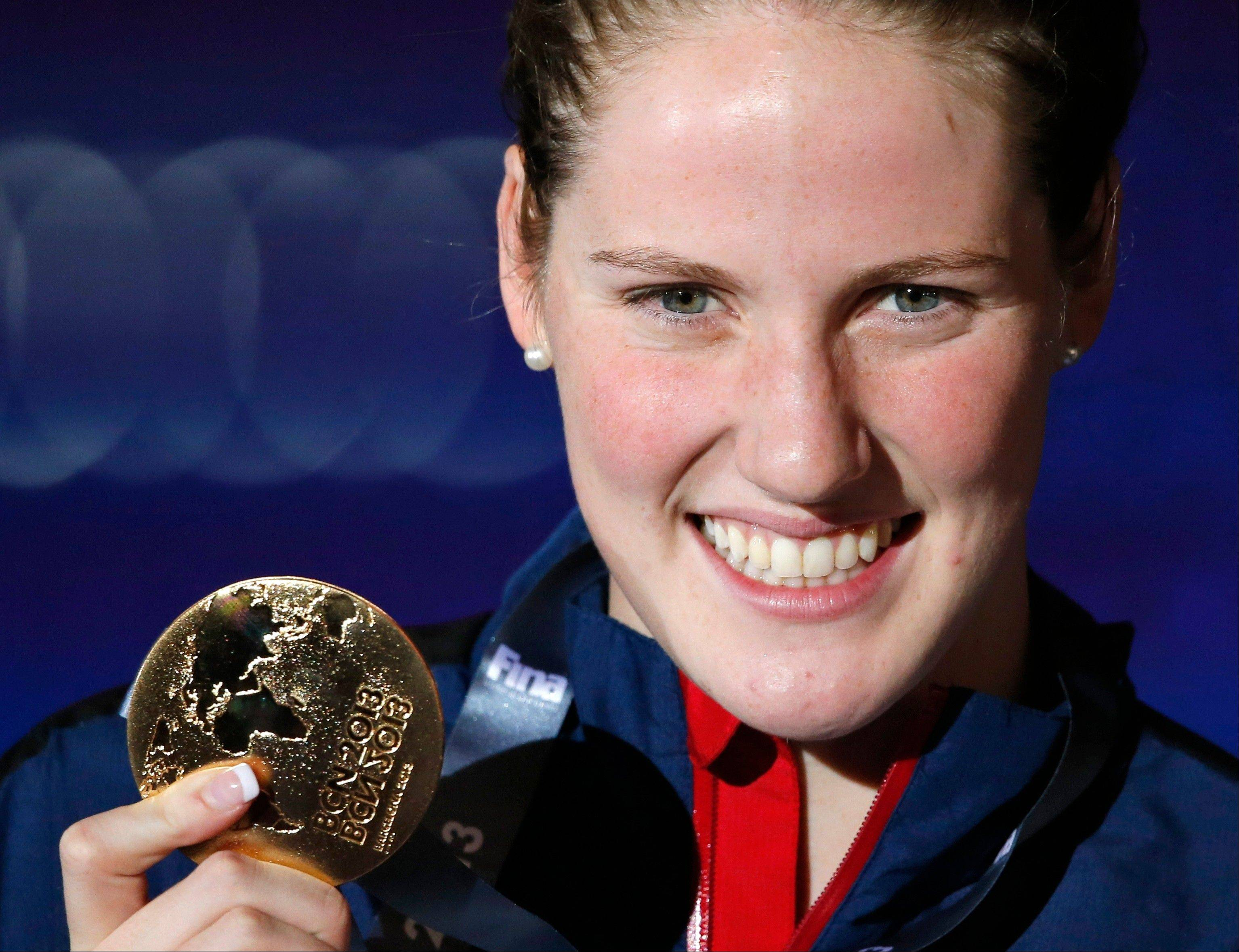 Missy Franklin of the United States smiles as she holds the gold medal she won in the Women's 200m backstroke final at the FINA Swimming World Championships in Barcelona, Spain, Saturday, Aug. 3, 2013. (AP Photo/Daniel Ochoa de Olza)