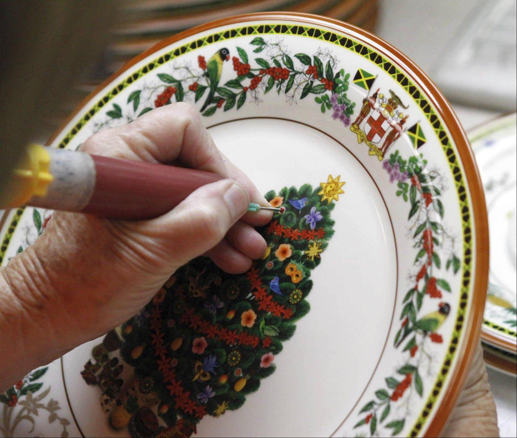 A painter adds color in extreme detail to a seasonal dish at the Lenox china factory in Kinston, N.C.