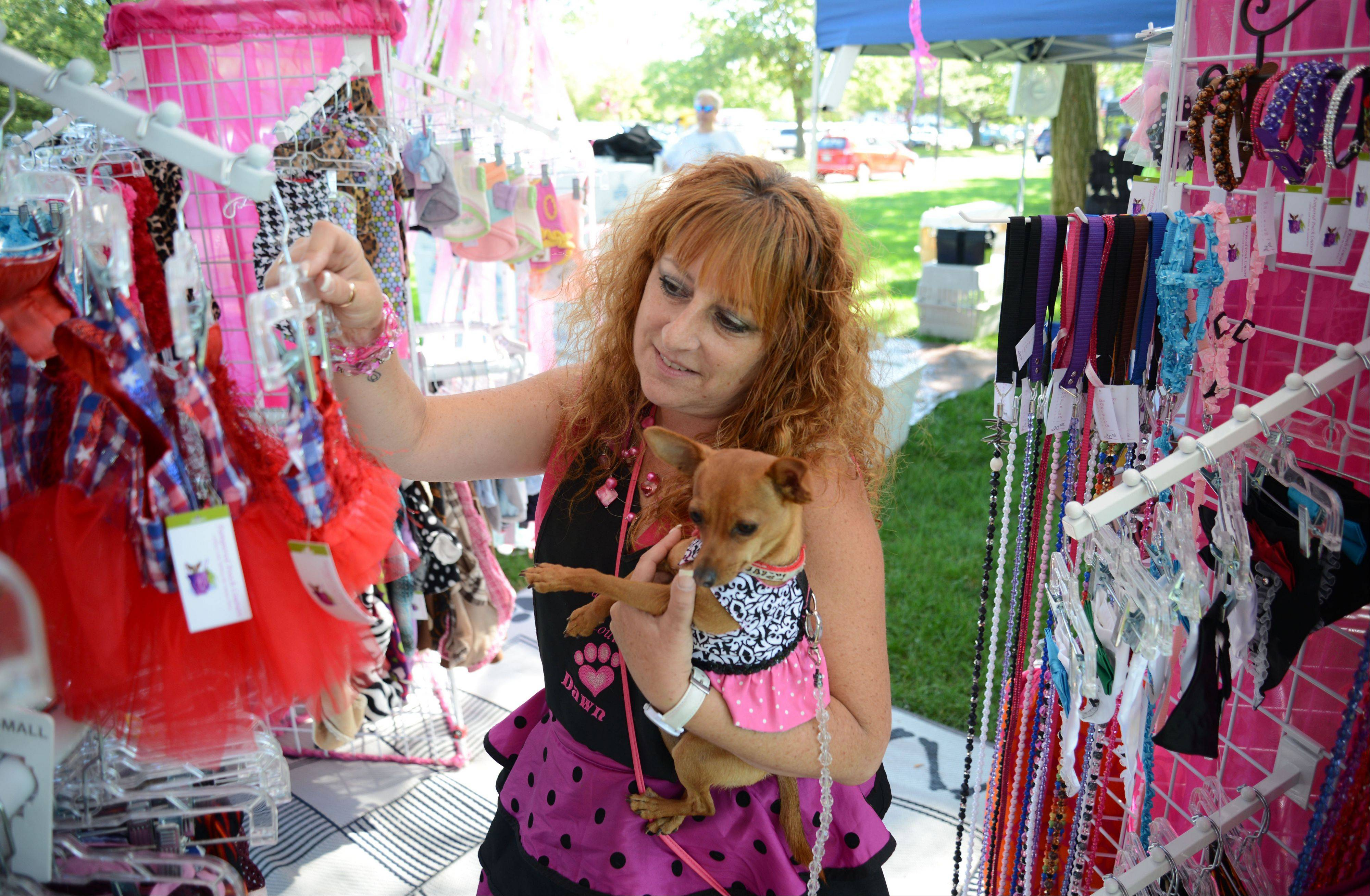 Dawn Kelsey and her dog look at items for sale at the Pampered Pooch Couture booth during the annual Dog Days celebration Saturday at Cantigny Park in Wheaton.