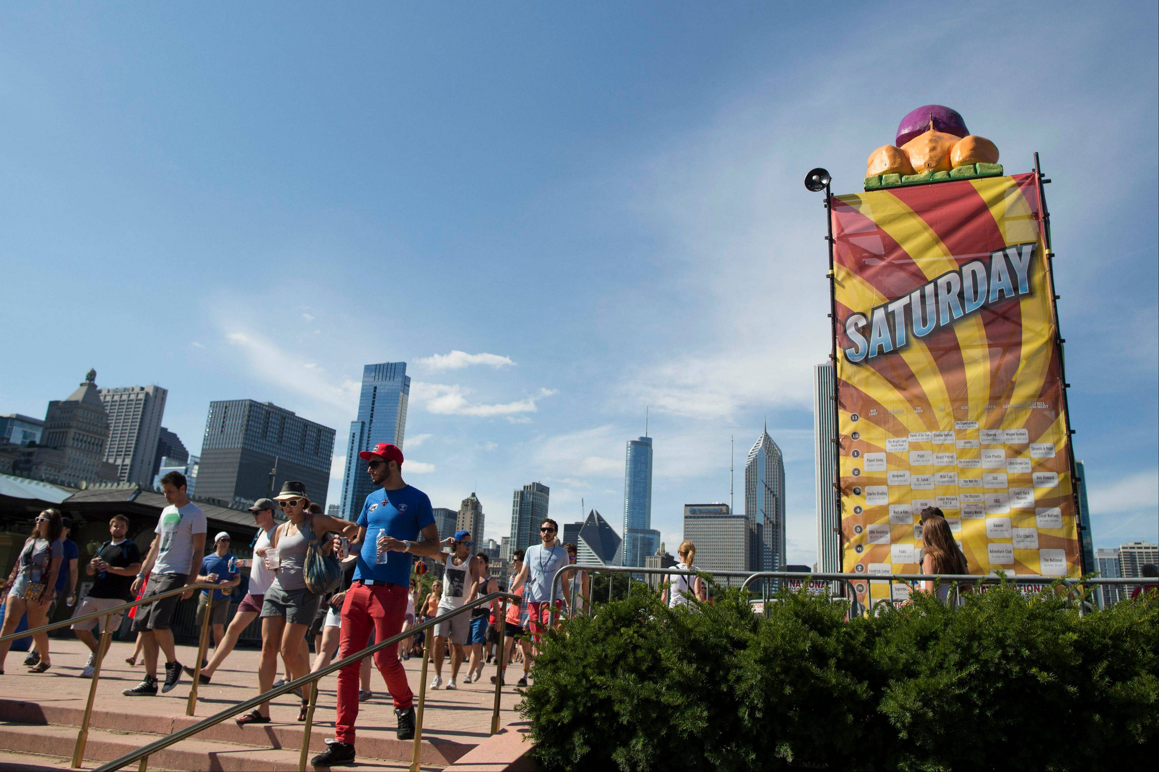 Festival attendees walk past a large Lollapalooza schedule at the Lollapalooza Festival in Chicago, Saturday, Aug. 3, 2013. The more than two-decade-old festival opened Friday in Chicago's lakefront Grant Park.