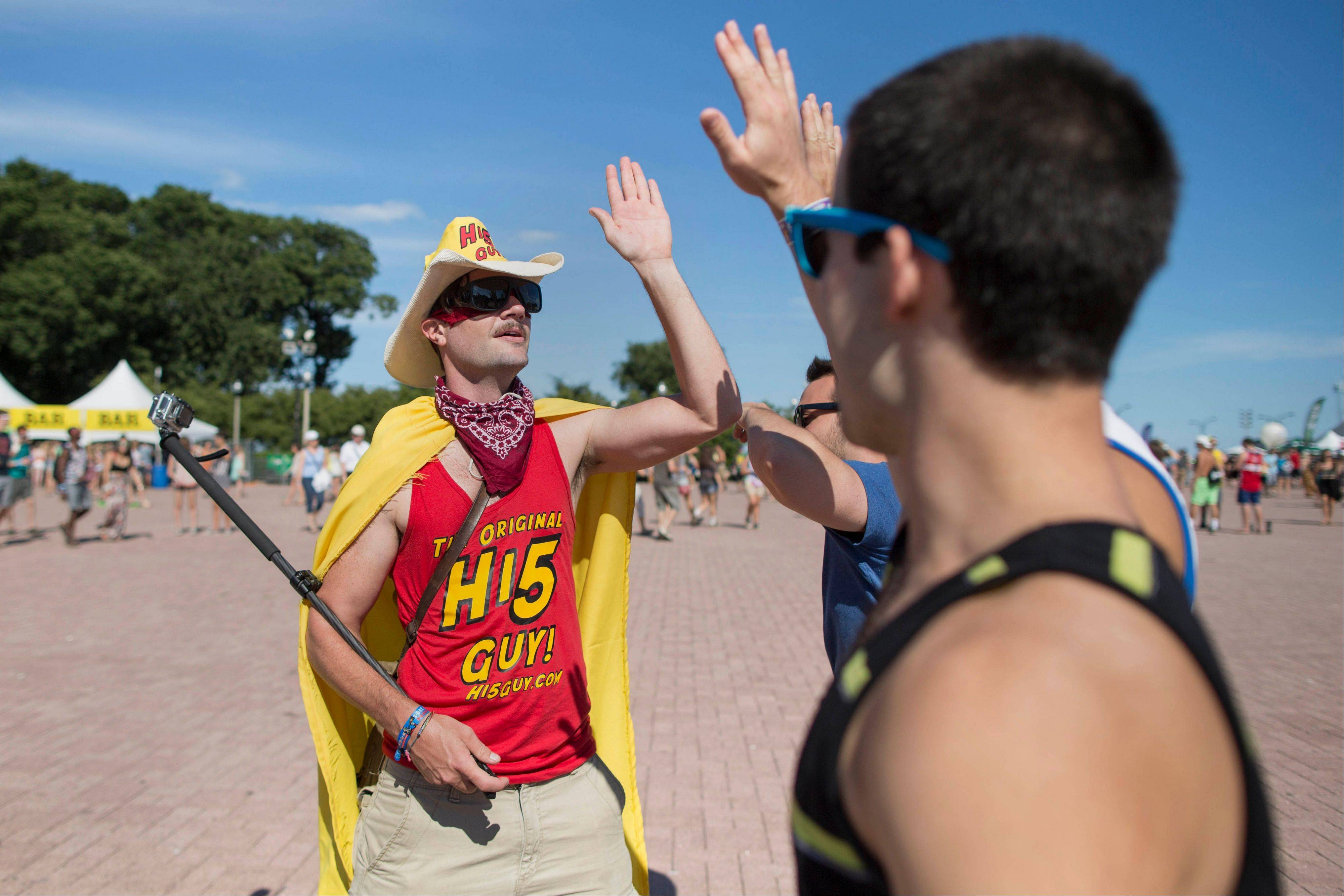 "Stretch Flemmings, who also goes by ""The Original Hi5 Guy"" gives high-fives to Festival attendees who walk past at the Lollapalooza Festival in Chicago, Saturday, Aug. 3, 2013. He is raising money for Los Angeles Children's Hospital. The more than two-decade-old festival opened Friday in Chicago's lakefront Grant Park."