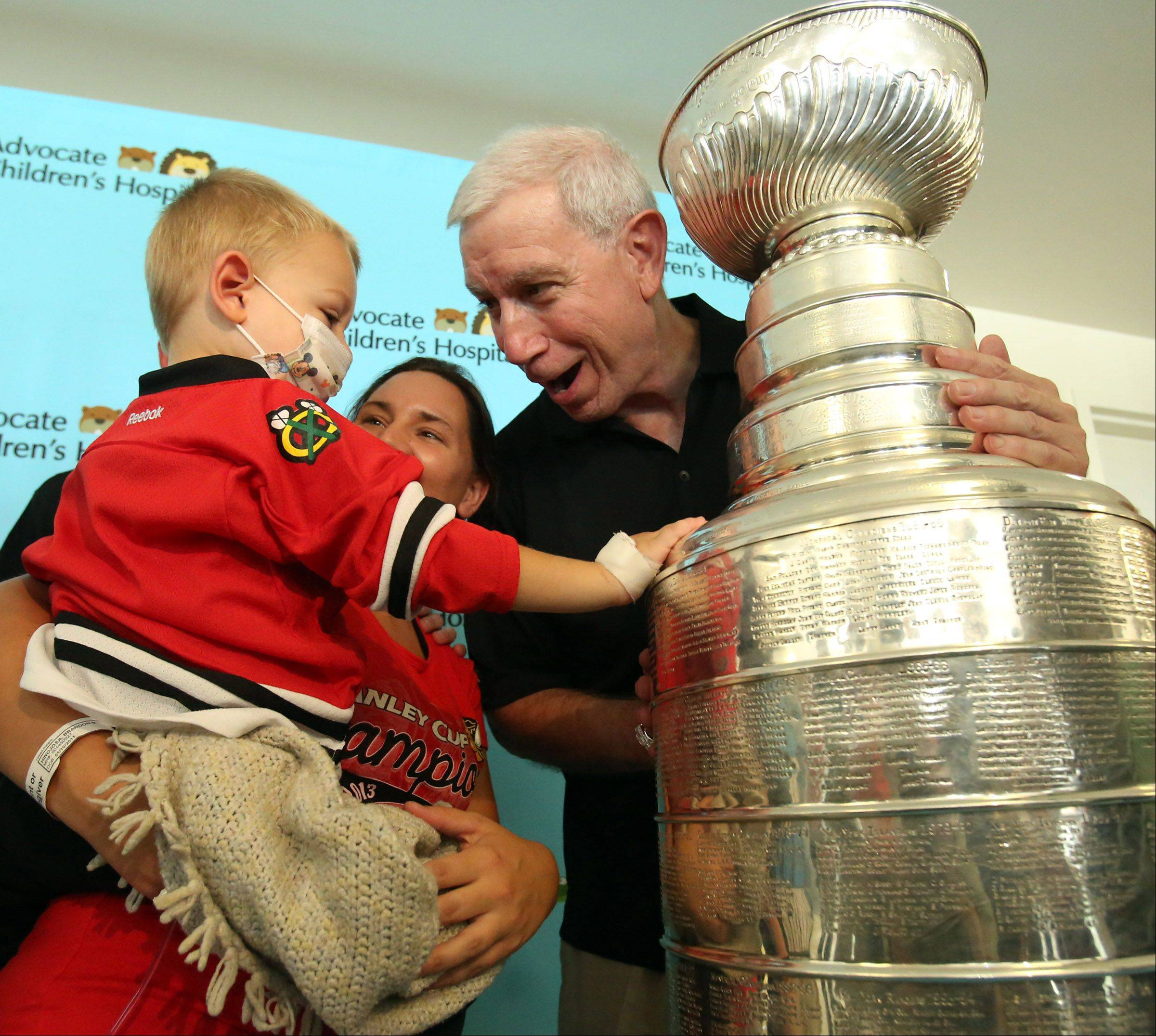 Two-year-old Brandon Hinojosa of Lake Zurich, who was diagnosed with leukemia two days ago, was a little shy while touching the Stanley Cup and posing for pictures with John McDonough, president and CEO of the Chicago Blackhawks. He's being held by his mother, Brandy, in the waiting area Saturday at Advocate Children's Hospital in Park Ridge.
