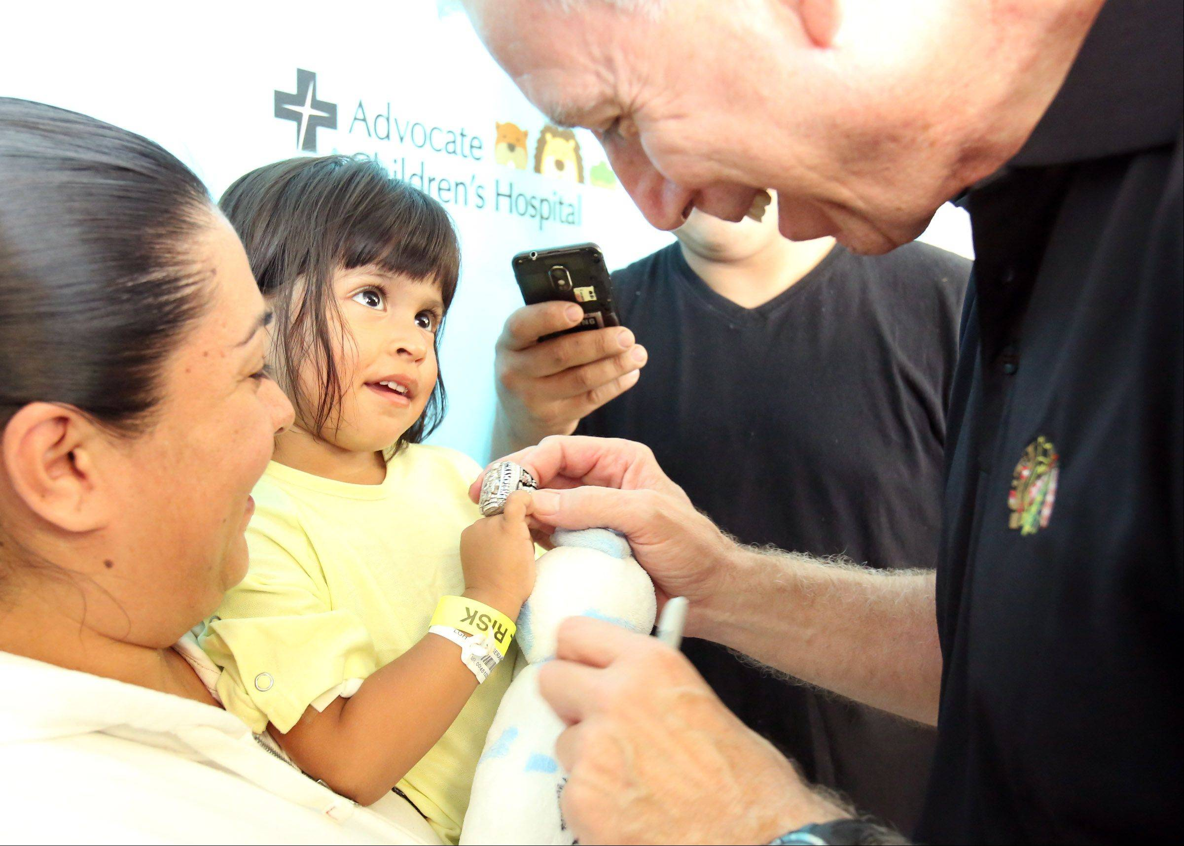 Chicago Blackhawks president and CEO John McDonough places his championship ring on 3-year-old Julia Ximena of Wonder Lake's finger. The ring brought a smile to her face as it slid around her small finger at Advocate Children's Hospital in Park Ridge on Saturday.