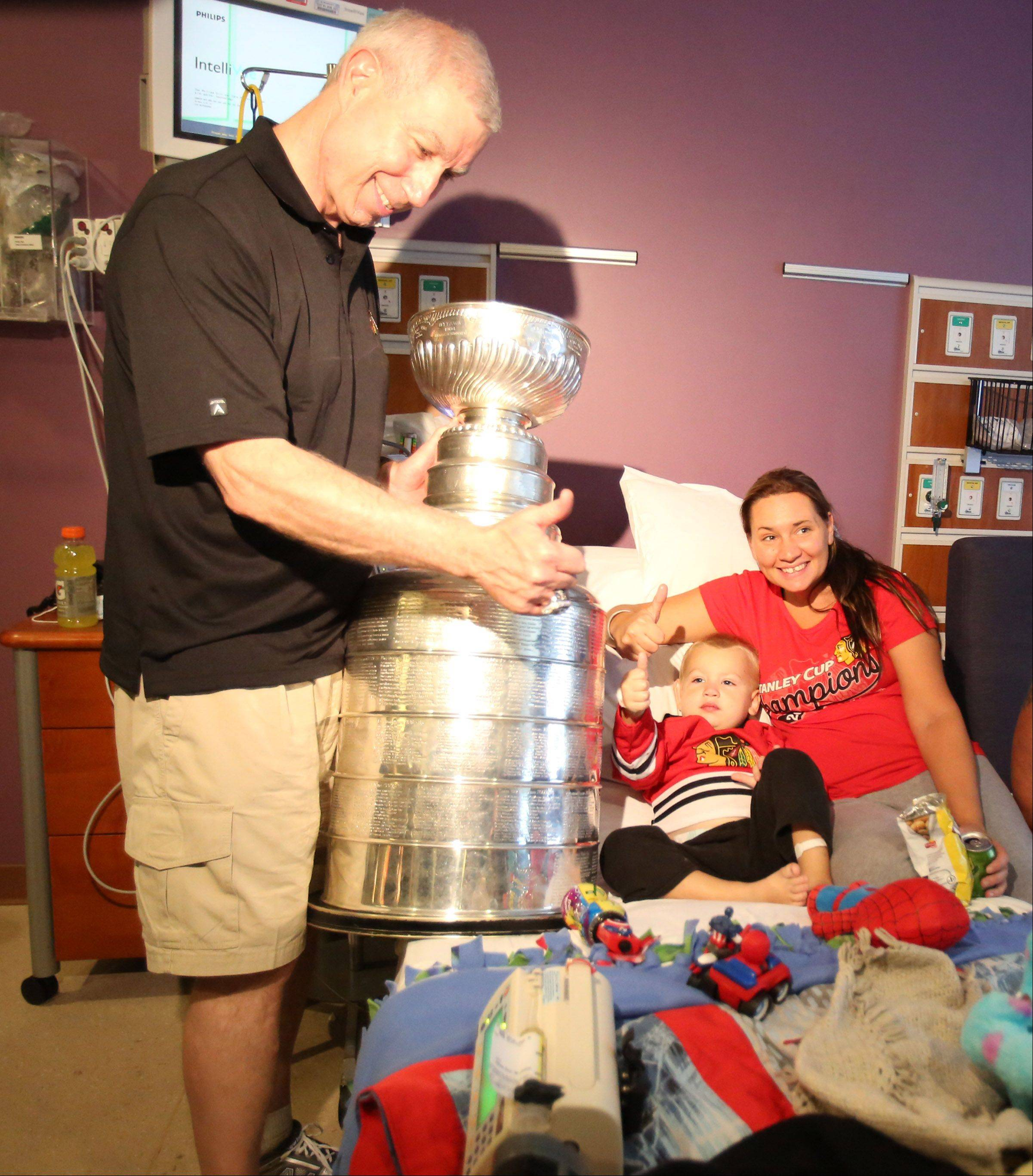 Two-year-old Brandon Hinojosa of Lake Zurich, who was diagnosed with leukemia two days ago, gives the thumbs-up when John McDonough, president and CEO of the Chicago Blackhawks brought the Stanley Cup to his room Saturday at Advocate Children's Hospital. Lying next to Brandon is his mother, Brandy.