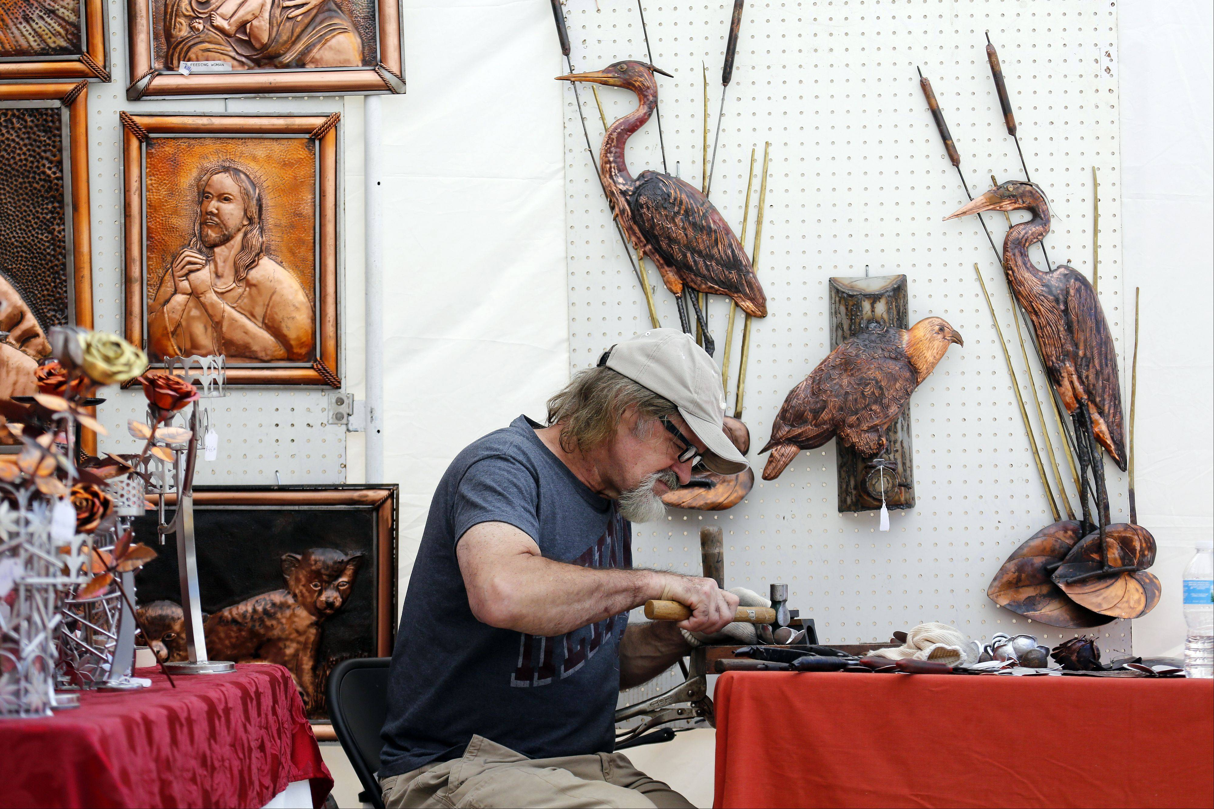 Surrounded by his artwork, Józef Andrzejczuk of Mount Prospect creates a rose from copper during Art & Soul on the Fox Saturday in Elgin. Andrzejczuk has been working in metal for more than 30 years and also does custom artwork.